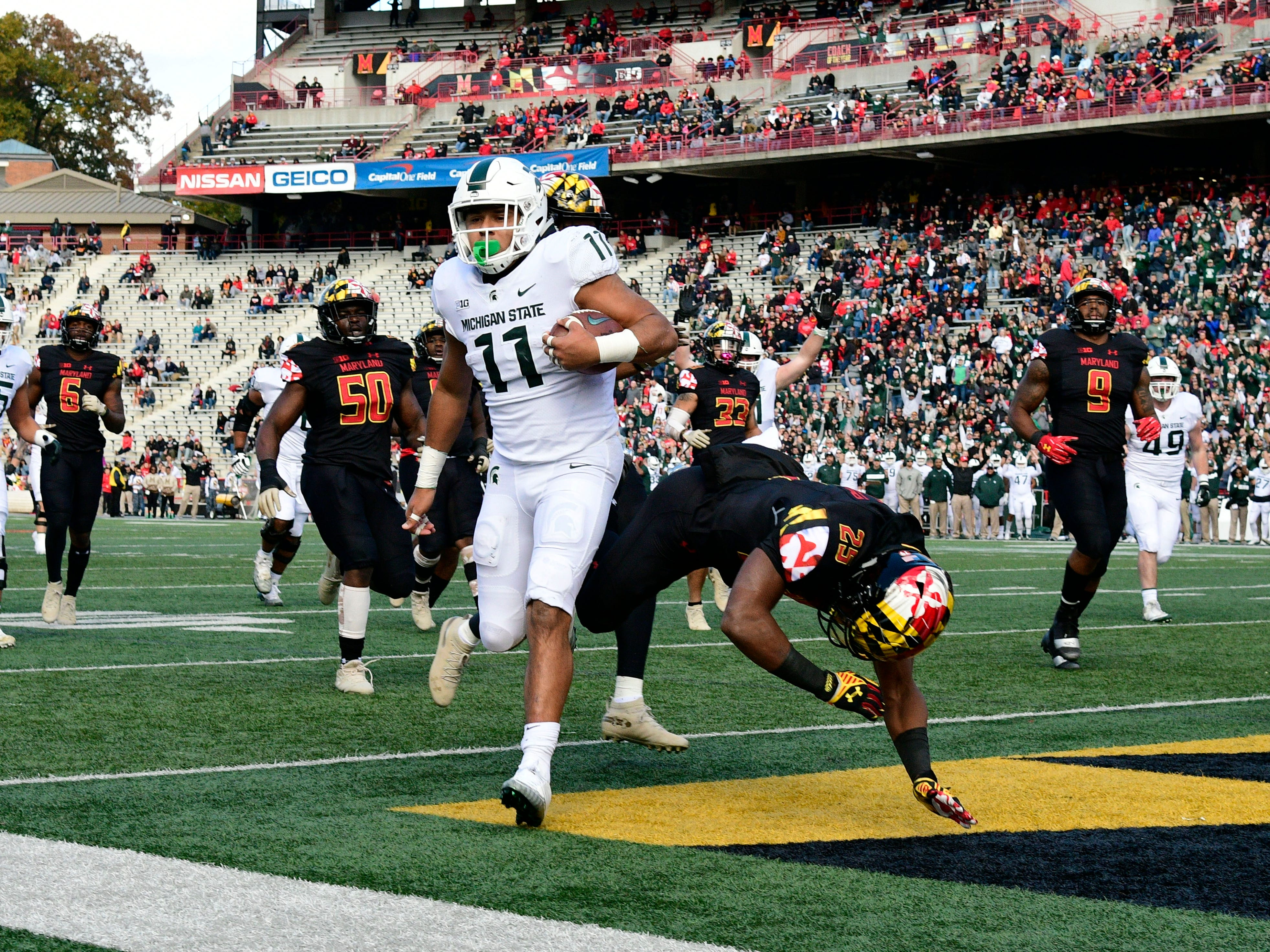 Michigan State Spartans running back Connor Heyward (11) runs past Maryland Terrapins defensive back Antoine Brooks Jr. (25) for a first down during the first quarter at Capital One Field at Maryland Stadium.