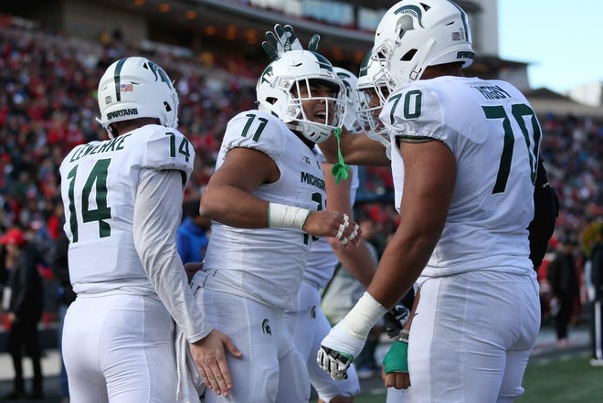 Connor Heyward #11 of the Michigan State Spartans celebrates with Tyler Higby #70 and Brian Lewerke #14 of the Michigan State Spartans after scoring a touchdown against the Maryland Terrapins during the first half at Capital One Field on November 3, 2018 in College Park, Maryland.