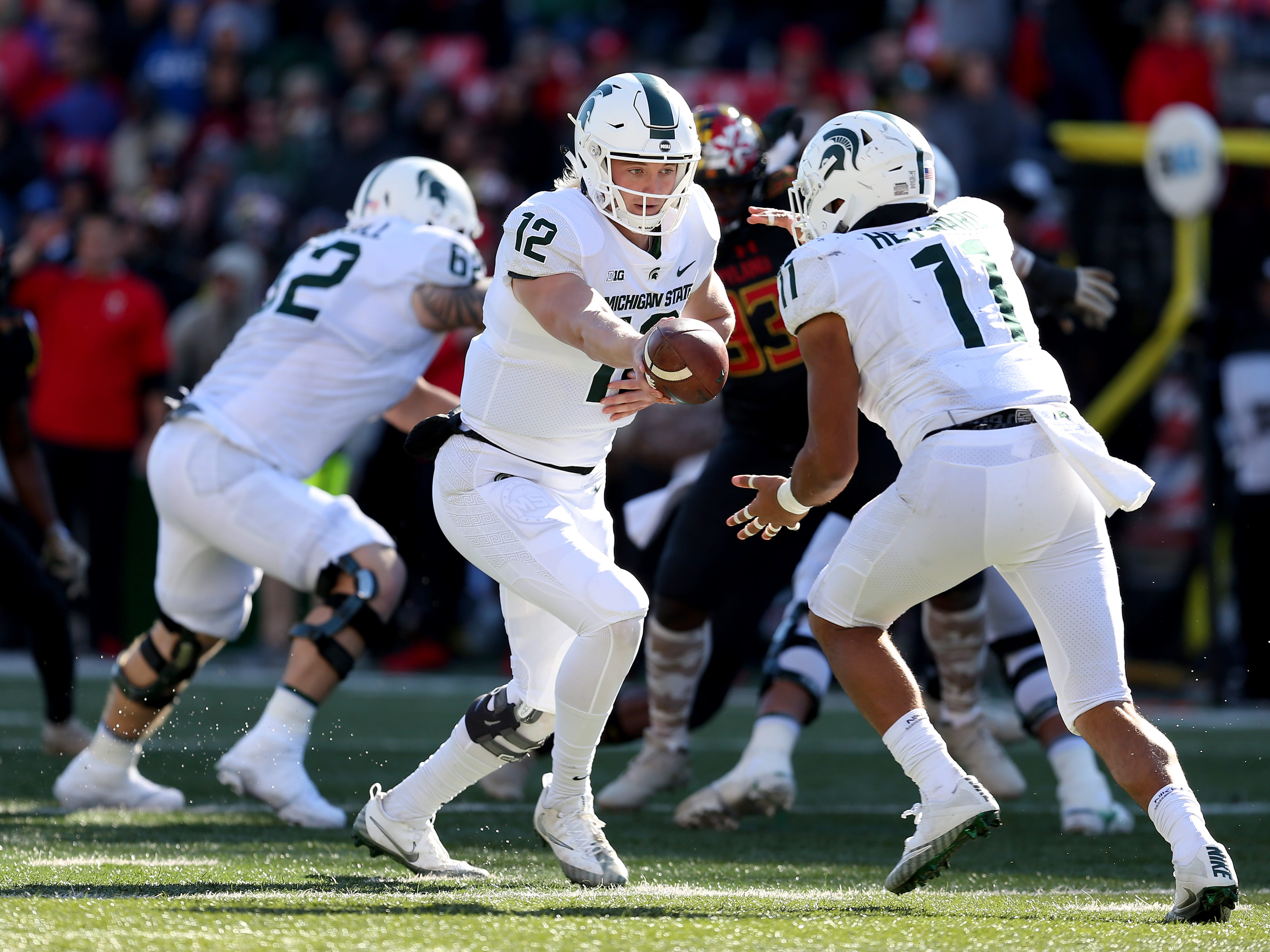 Rocky Lombardi #12 of the Michigan State Spartans hands the ball off to Connor Heyward #11 of the Michigan State Spartans during the second half against the Maryland Terrapins at Capital One Field on November 3, 2018 in College Park, Maryland.
