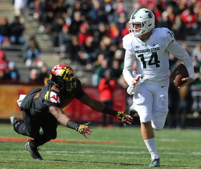 Michigan State quarterback Brian Lewerke (14) eludes Maryland's Antoine Brooks in the first half of an NCAA college football game, Saturday, Nov. 3, 2018, in College Park, Md.