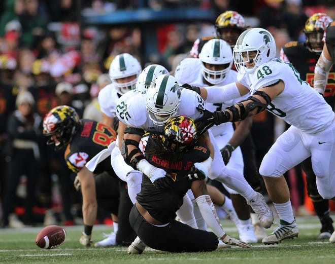 Maryland running back Anthony McFarland, center, fumbles while being tackled by Michigan State's defense in the first half Saturday.