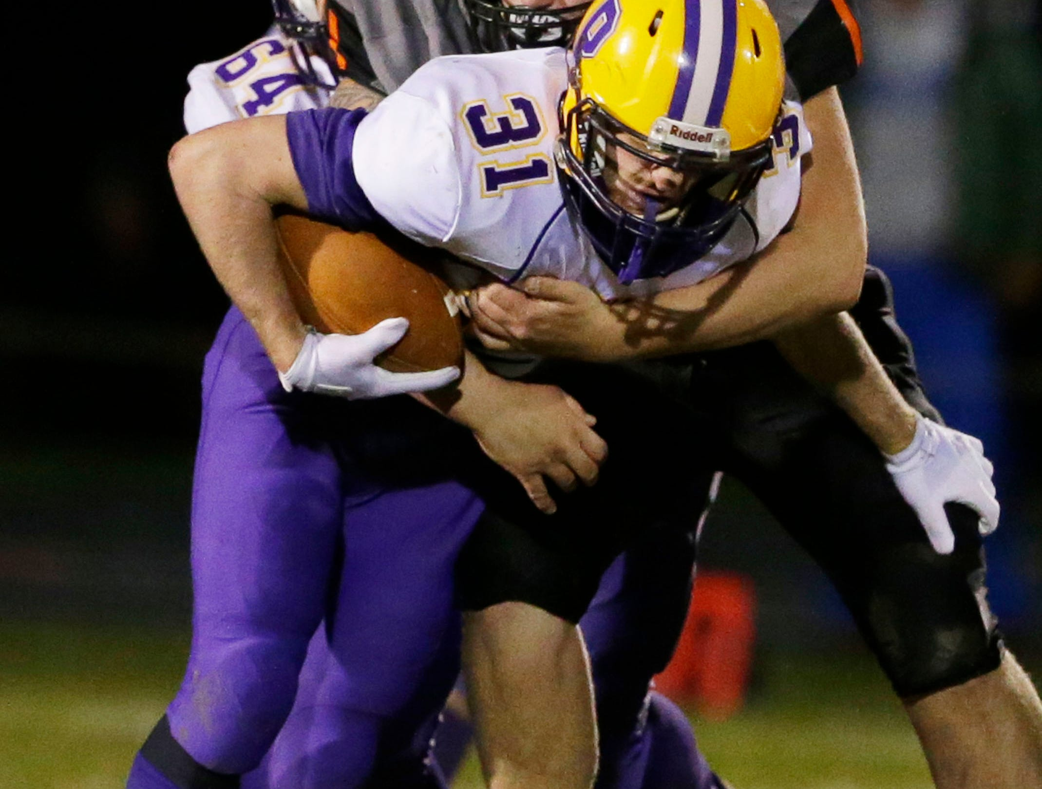 Pittsville's Trayson Ortner (31) is pulled down by a Reedsville player, Friday, November 2, 2018, in Reedsville, Wis.