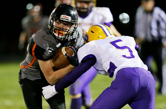 Reedsville's Brandon Steltzer (34) carries the ball in front of Pittsville's Evan Dammann during Friday's WIAA quarterfinal playoff game in Reedsville.