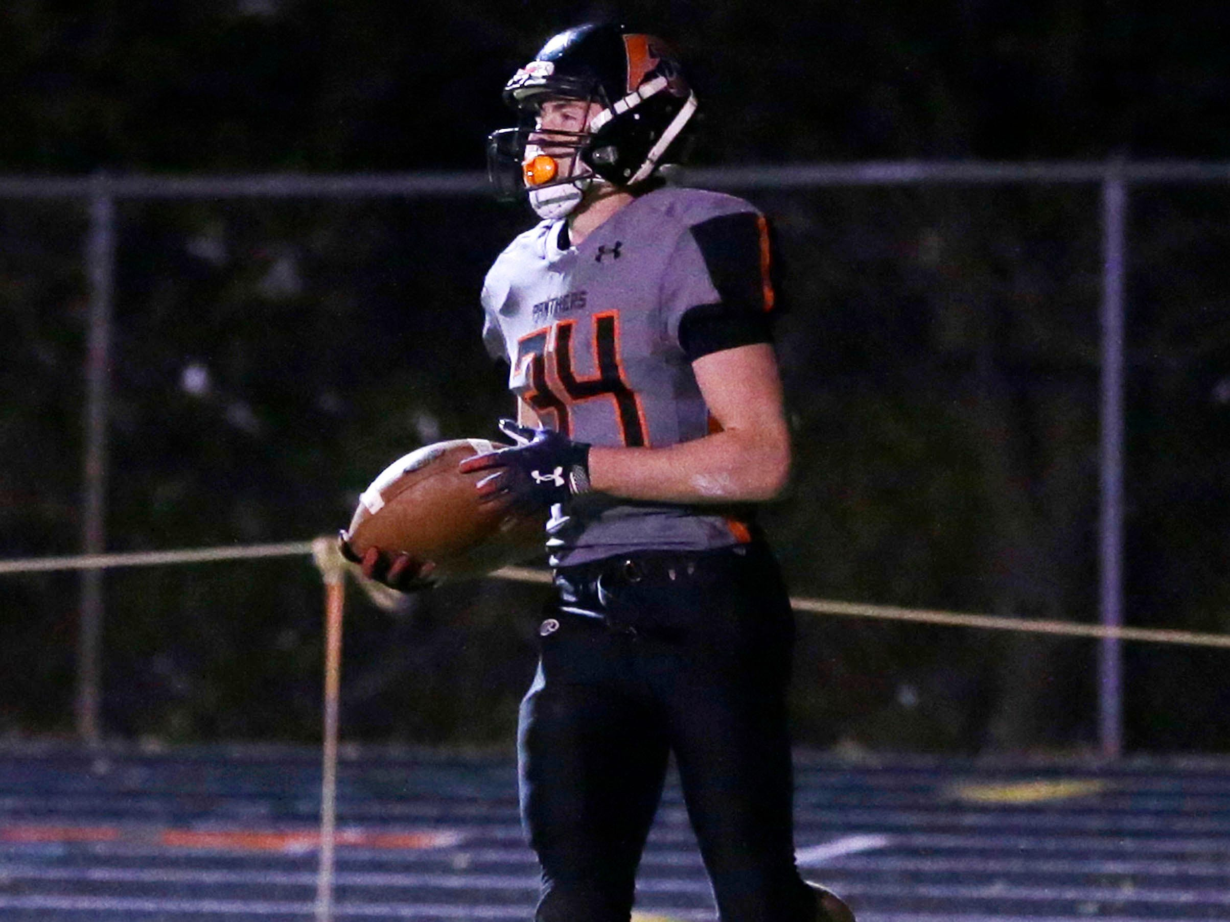 Reedsville's Brandon Stelzer (34) carries the ball in the end zone after scoring a touchdown against Pittsville, Friday, November 2, 2018, in Reedsville, Wis.