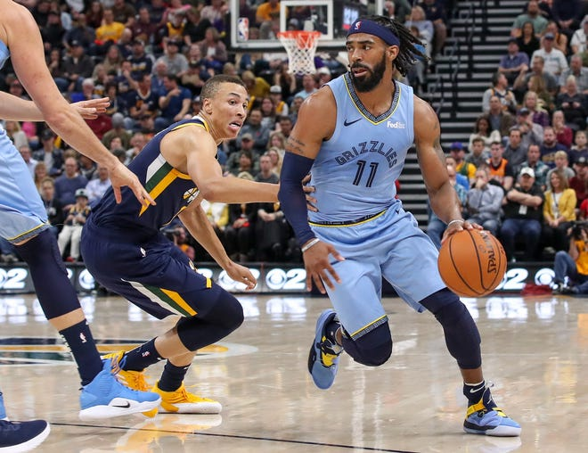 Grizzlies guard Mike Conley (11) dribbles away from Utah Jazz guard Dante Exum (11) during the second quarter at Vivint Smart Home Arena.