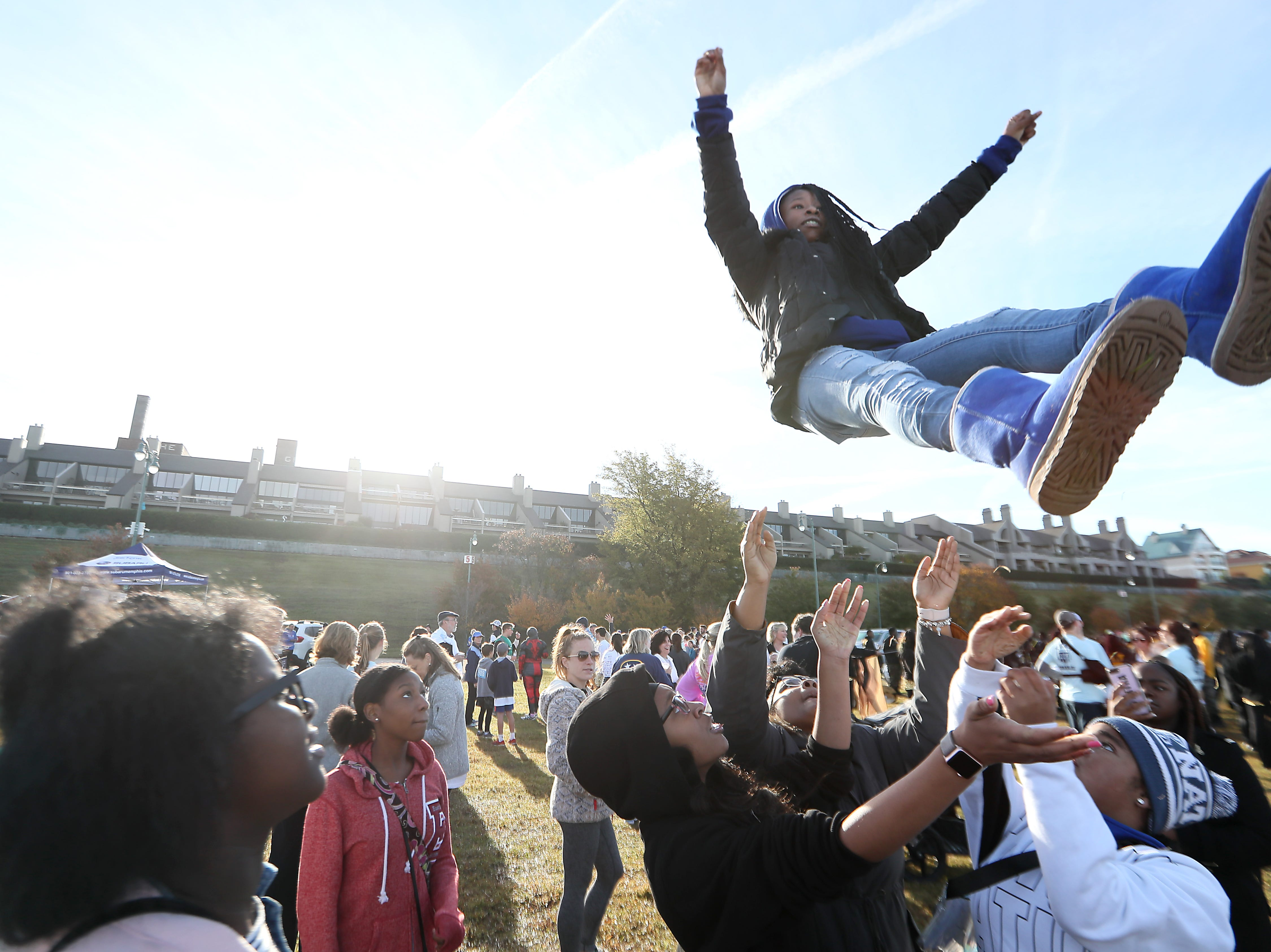 Halei Webb, 14, performs a stunt with the Eastside Cheerleaders at the finish line of the Big River Crossing Half-Marathon and 5K run downtown Memphis Saturday, November 3, 2018.