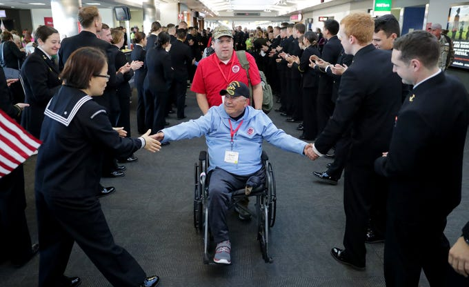 Vietnam veteran Ronald Tourtillott, with  his guardian Ricky Tourtillott, is greeted Saturday by midshipmen from the United States Naval Academy in Annapolis, Maryland, after getting off a southeastern Wisconsin Stars and Stripes Honor Flight in Baltimore.  Ronald Tourtillott is among 145 veterans who flew on two chartered planes to visit World War II and Korean War monuments and the Vietnam Wall in Washington, D.C., and Arlington National Cemetery to witness the changing of the guard at the Tomb of the Unknown Soldier.