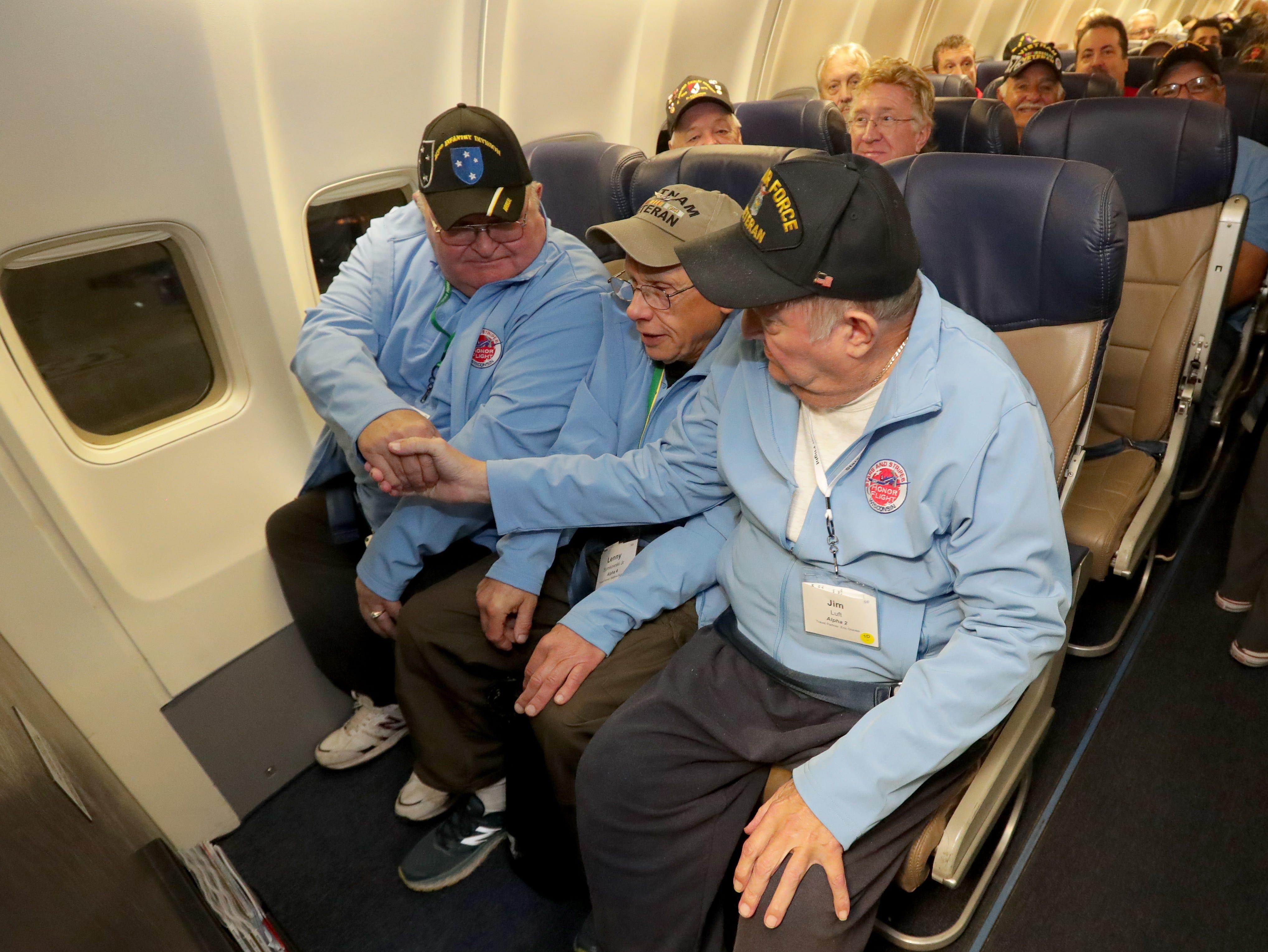 Vietnam War veterans John Dahl (from left), Lenny Symkowski and Jim Luft introduce themselves on the plane.