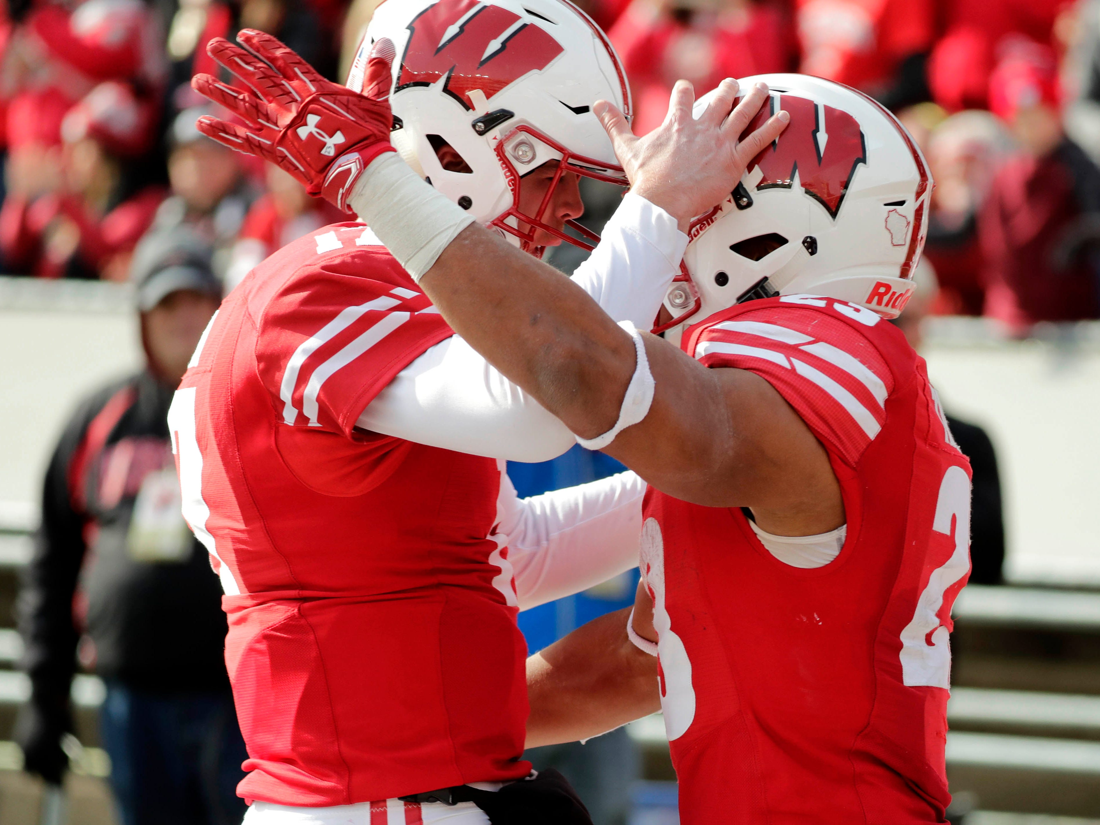 Badgers running back Jonathan Taylor (right) celebrates one of his touchdown scampers in the second half against Rutgers with backup quarterback Jack Coan on Saturday.