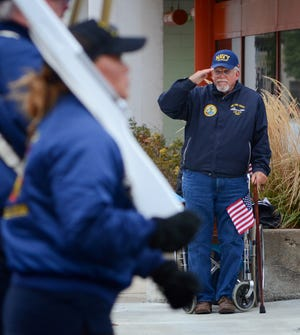 Navy veteran Ralph Kessler of St. Francis steps out of his wheelchair to salute as the 2017 Veterans Day Parade passes. The 2018 parade is Saturday.