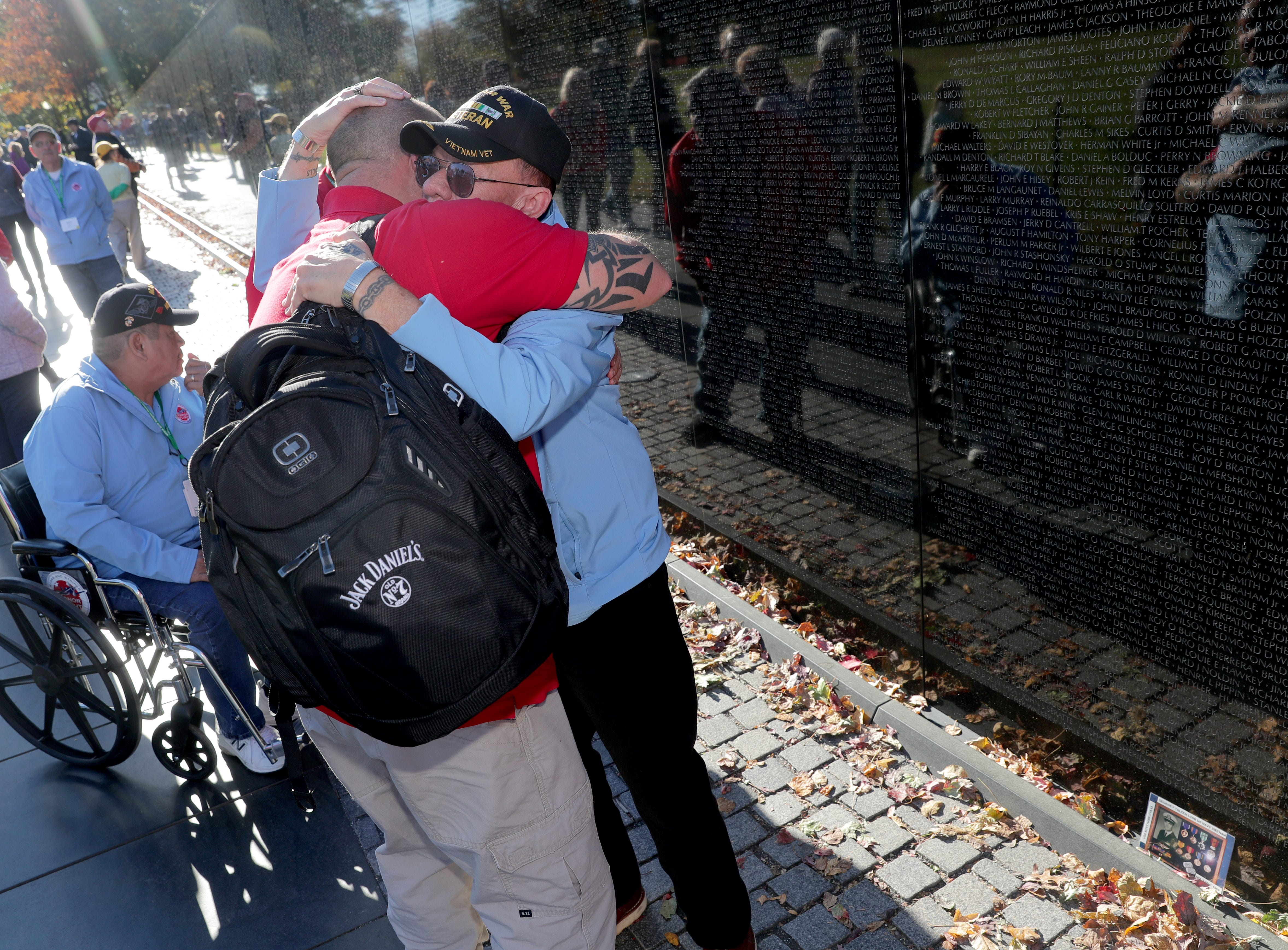 Vietnam Navy veteran Ranson Blanchard (right) of Elkhorn gets a hug from his son and Honor Flight guardian Wayne Blanchard, also of Elkhorn, at the Vietnam Veterans Memorial after fining his fellow Navy man's name on the wall.