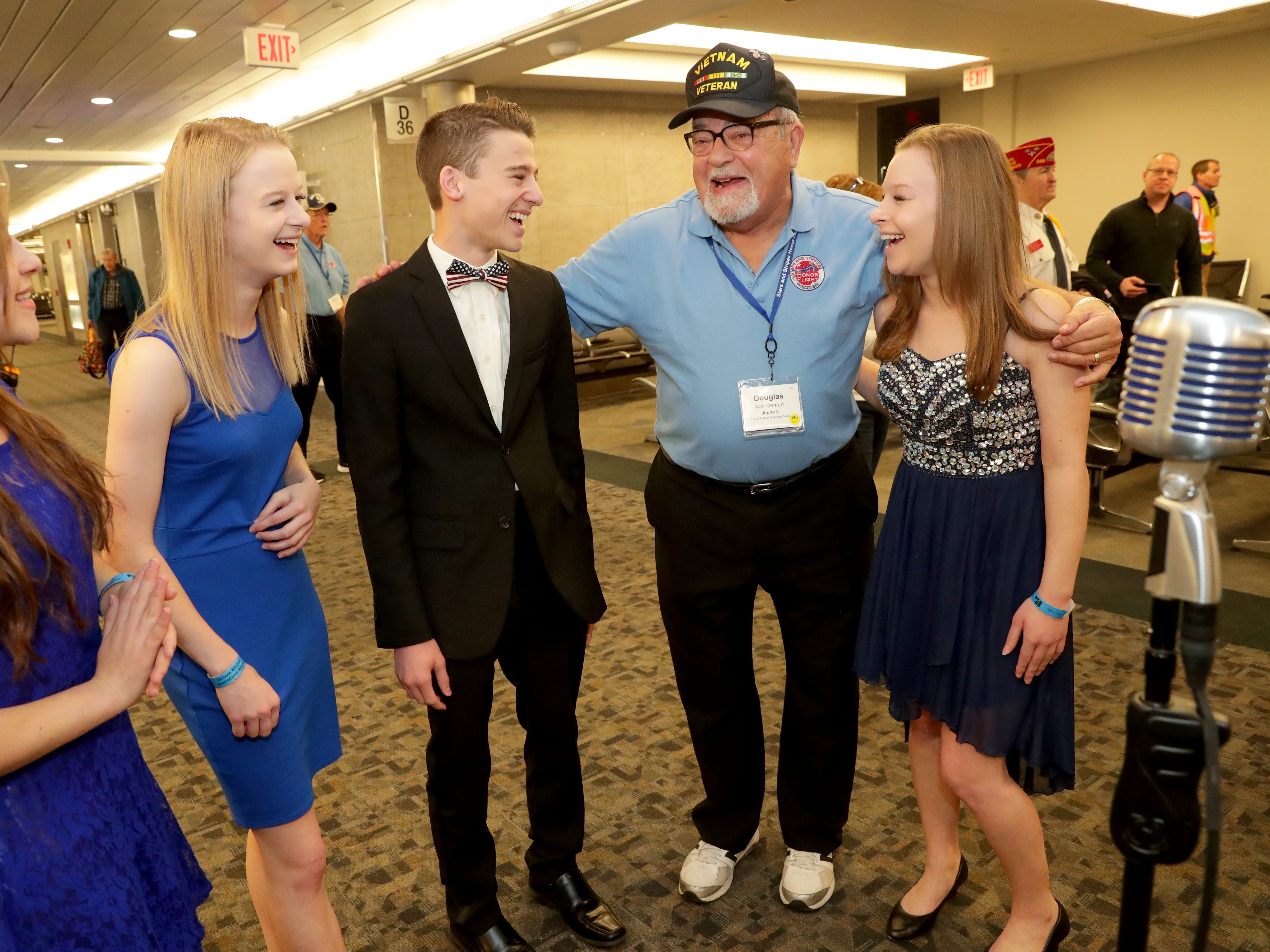 Vietnam veteran Douglas Van Gemert of Franklin poses for a photo with the quadruplet quartet singing group Vintage Mix, from Waukesha. The singers are  Julia Shoppach (from left), Anika Shoppach, Ian Shoppach and Kelsey Shoppach. The family has been performing for honor flight sendoffs since 2014.