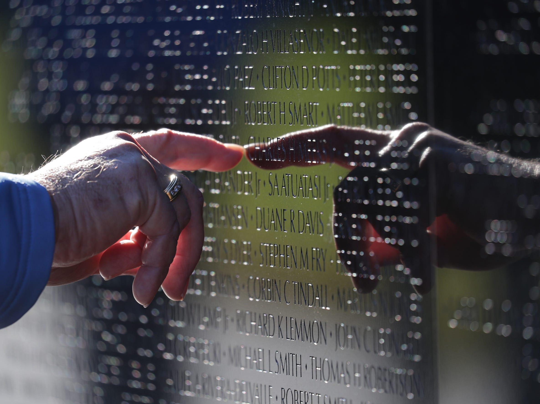 Vietnam Navy veteran Wally Beck of Norwalk, Wisconsin, looks up a neighbor's name at the Vietnam Veterans Memorial.