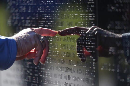 Vietnam Navy veteran Wally Beck of Norwalk looks up a neighbor's name Saturday at the Vietnam Veterans Memorial.