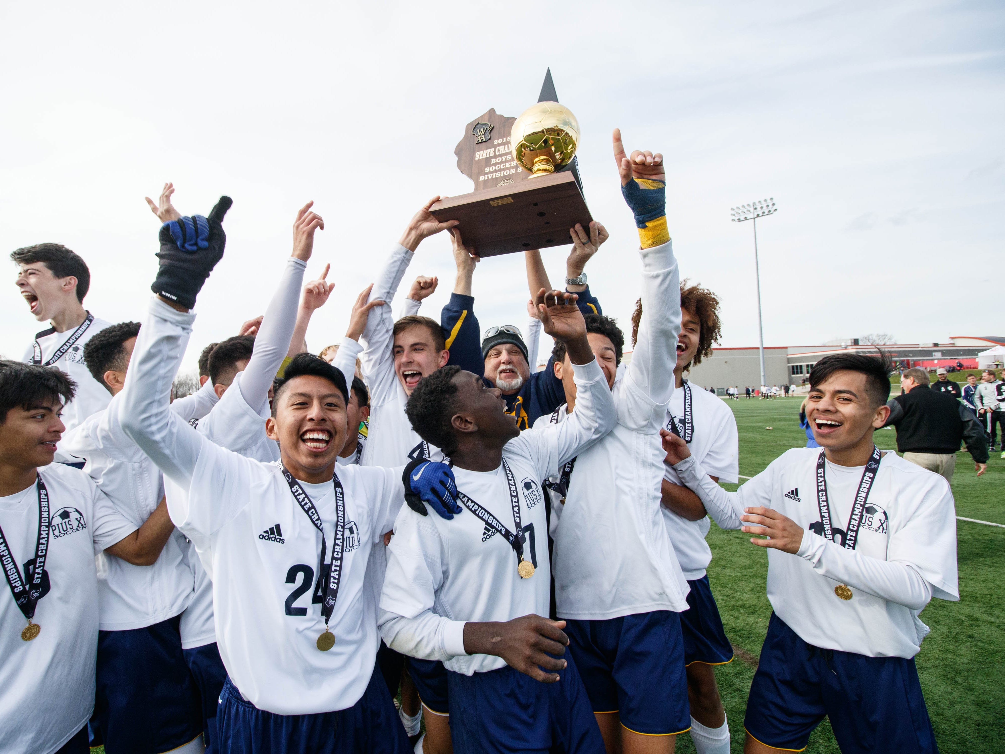 Pius XI head coach Hansi Herzog hoists the gold ball as his team celebrates winning the the WIAA Division 3 state soccer title with a 3-1 win over McFarland on Saturday at Uihlein Soccer Park in Milwaukee.