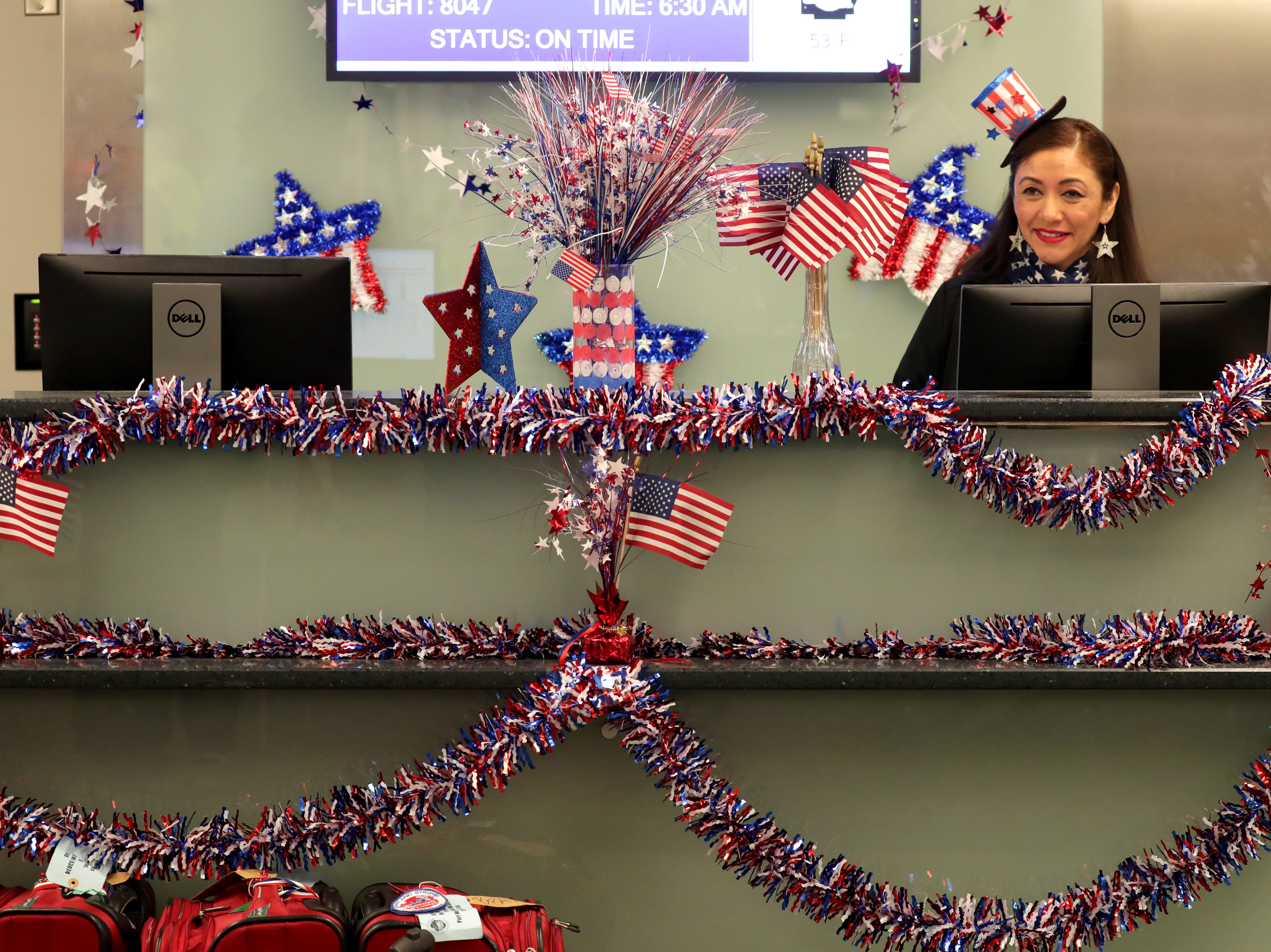 Southwest Airlines operations agent Daisy Rosas and the check-in counter are decked out in patriotic colors as she waits to check in passengers.