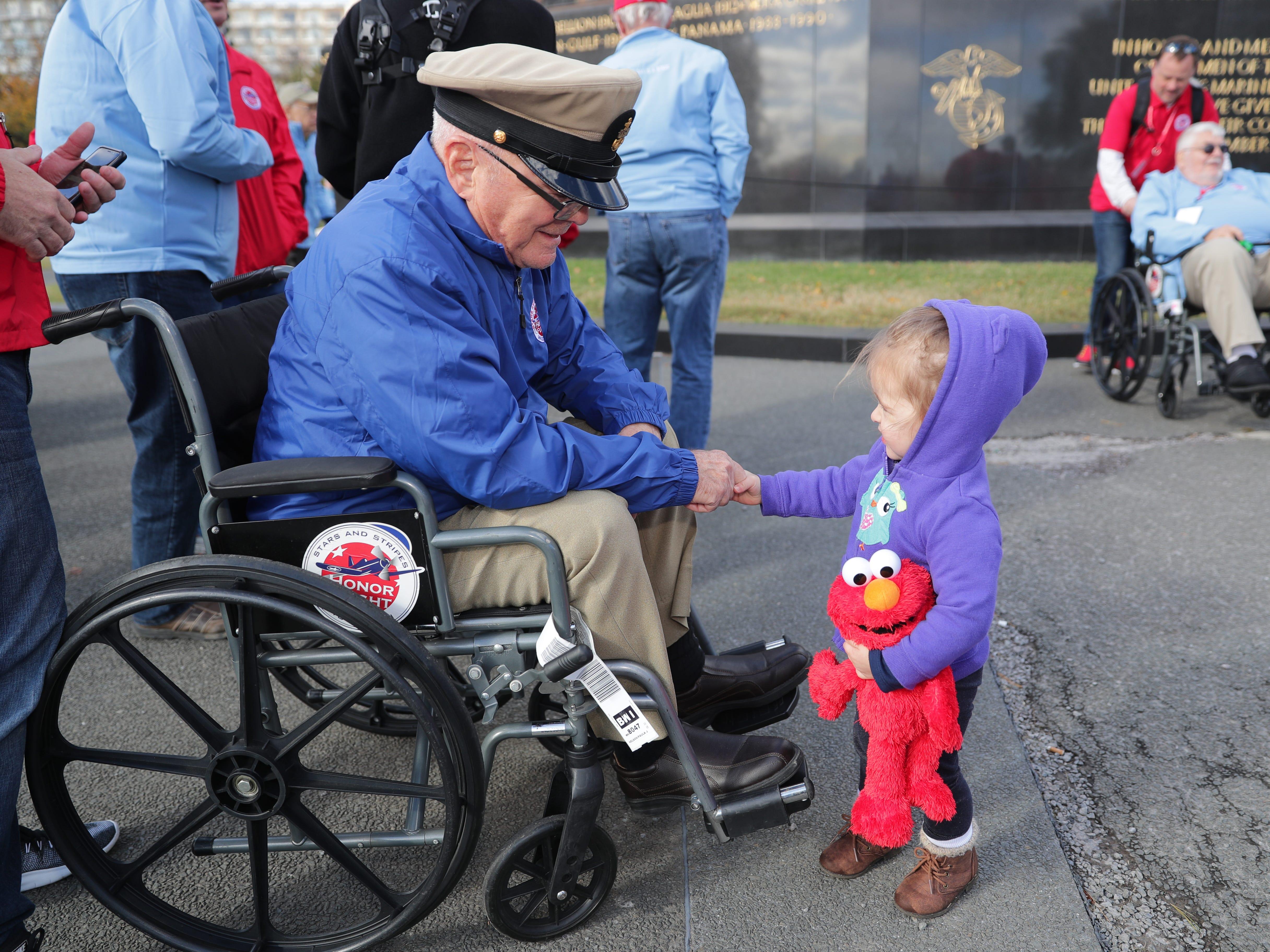 Two-year-old Jersey Ponzar of Arlington,  Virginia, greets Vince Lewein of  Oconomowoc at the Marine Corps Memorial in Arlington. Ponzar was with her dad Sammy Ponzar. Lewein is a 1955 to 1971 Korea- and Vietnam-era veteran.