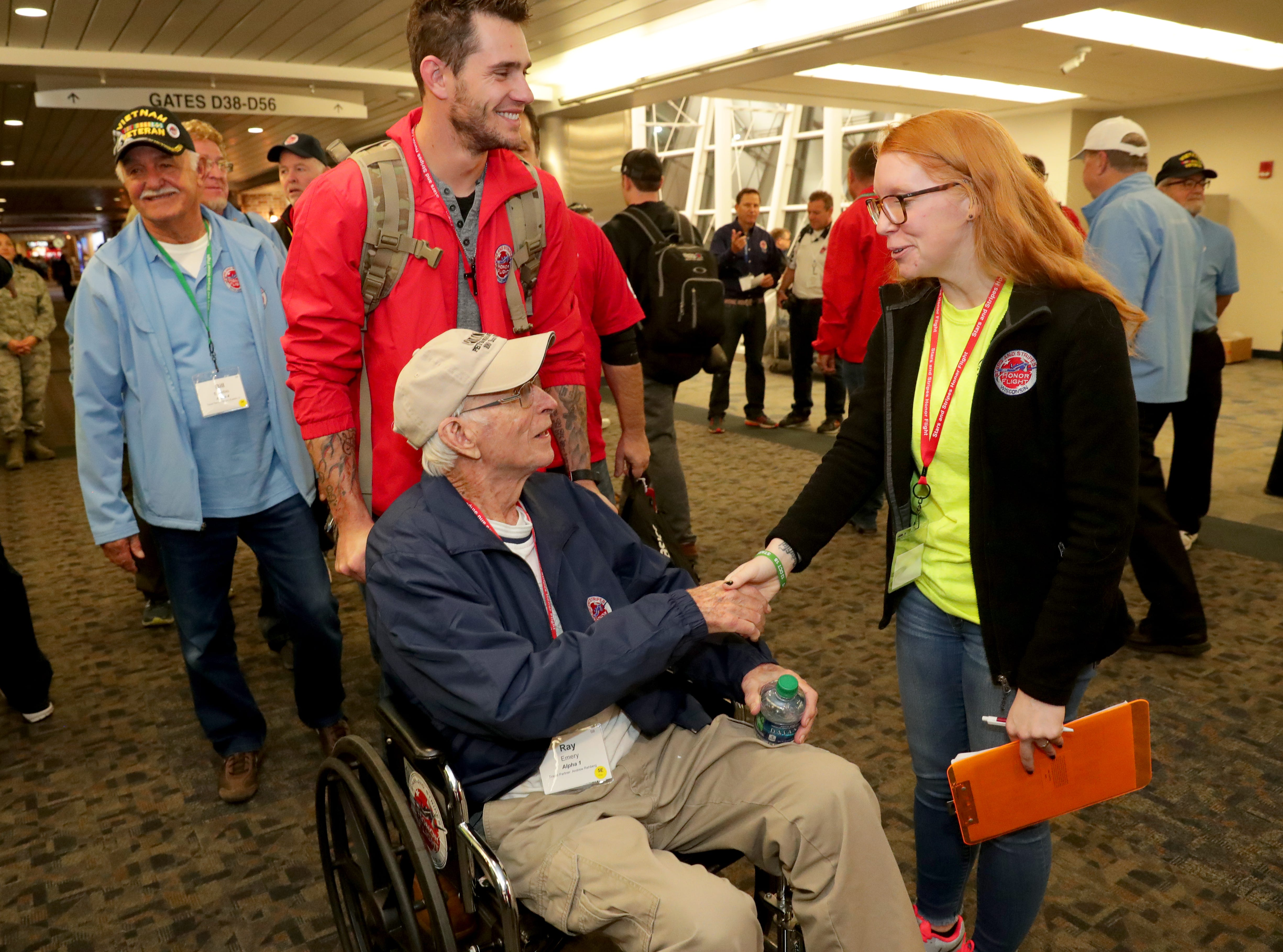 World War II Army veteran Ray Emery, 96, is greeted by Honor Flight volunteer, Erin Ball as Emery's grandson, Andrew Rehberg, who served two deployments in Afghanistan, 2010-'11 and 2012-'13, and in Kuwait, 2016-'17, serves as his guardian, before the flight departed from Milwaukee.