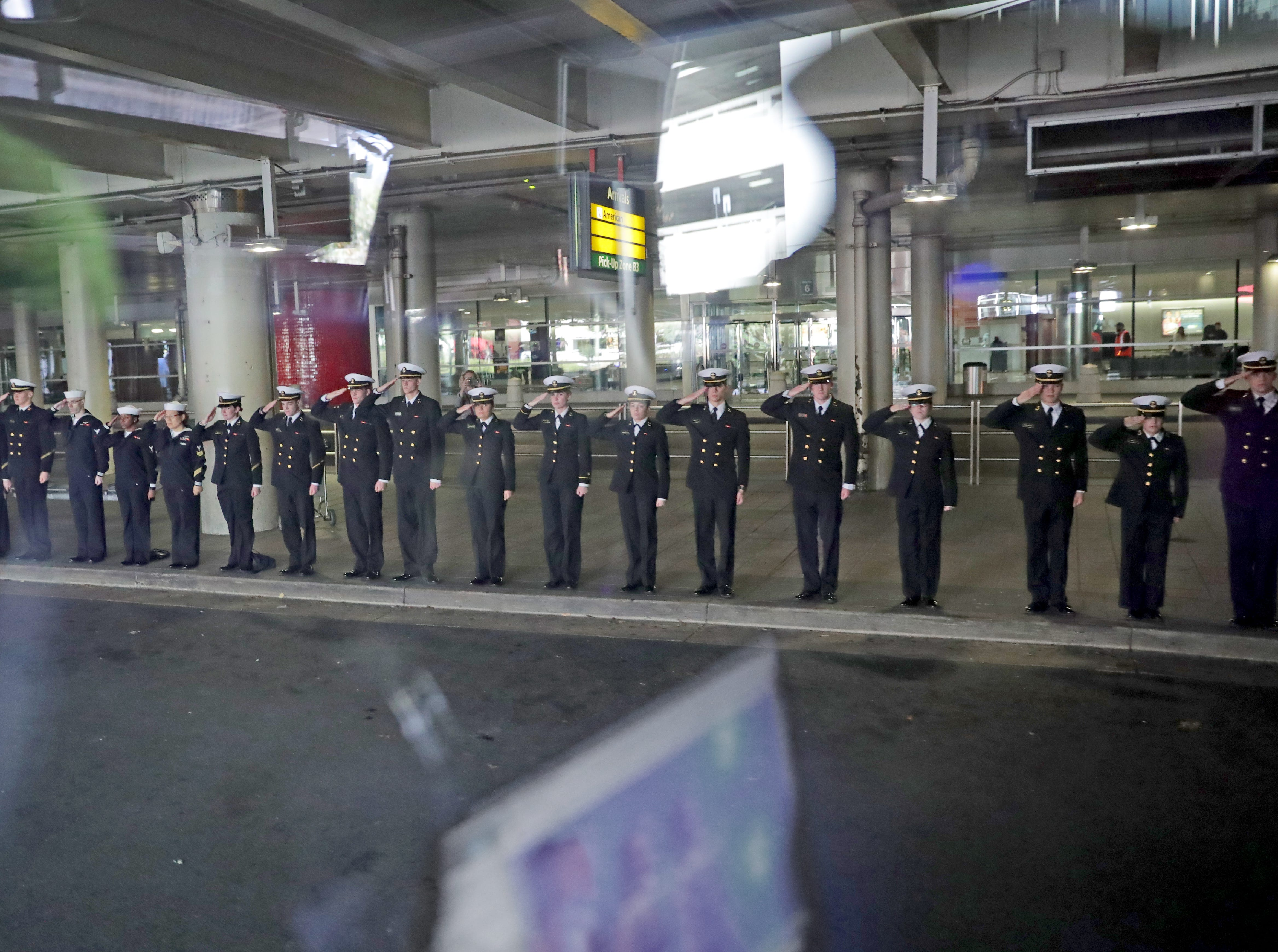 Midshipmen from the  Naval Academy  salute a bus full of Honor Flight veterans as it passes while leaving the Baltimore airport.