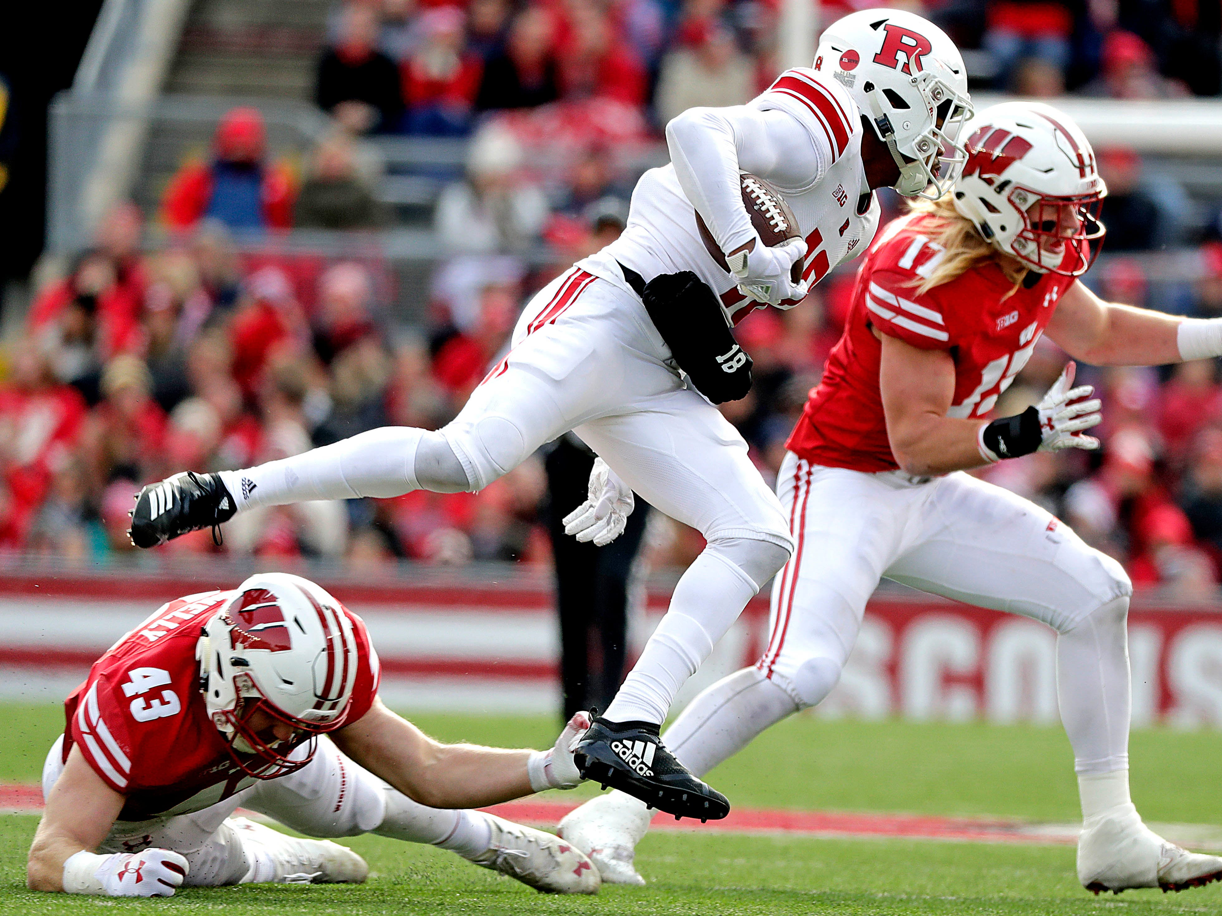 UW linebacker Ryan Connelly (43) trips up Scarlet Knights wide receiver Bo Melton on Saturday.