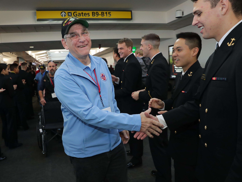 Vietnam veteran John Kleinmaus of West Bend shakes hands with a midshipman.