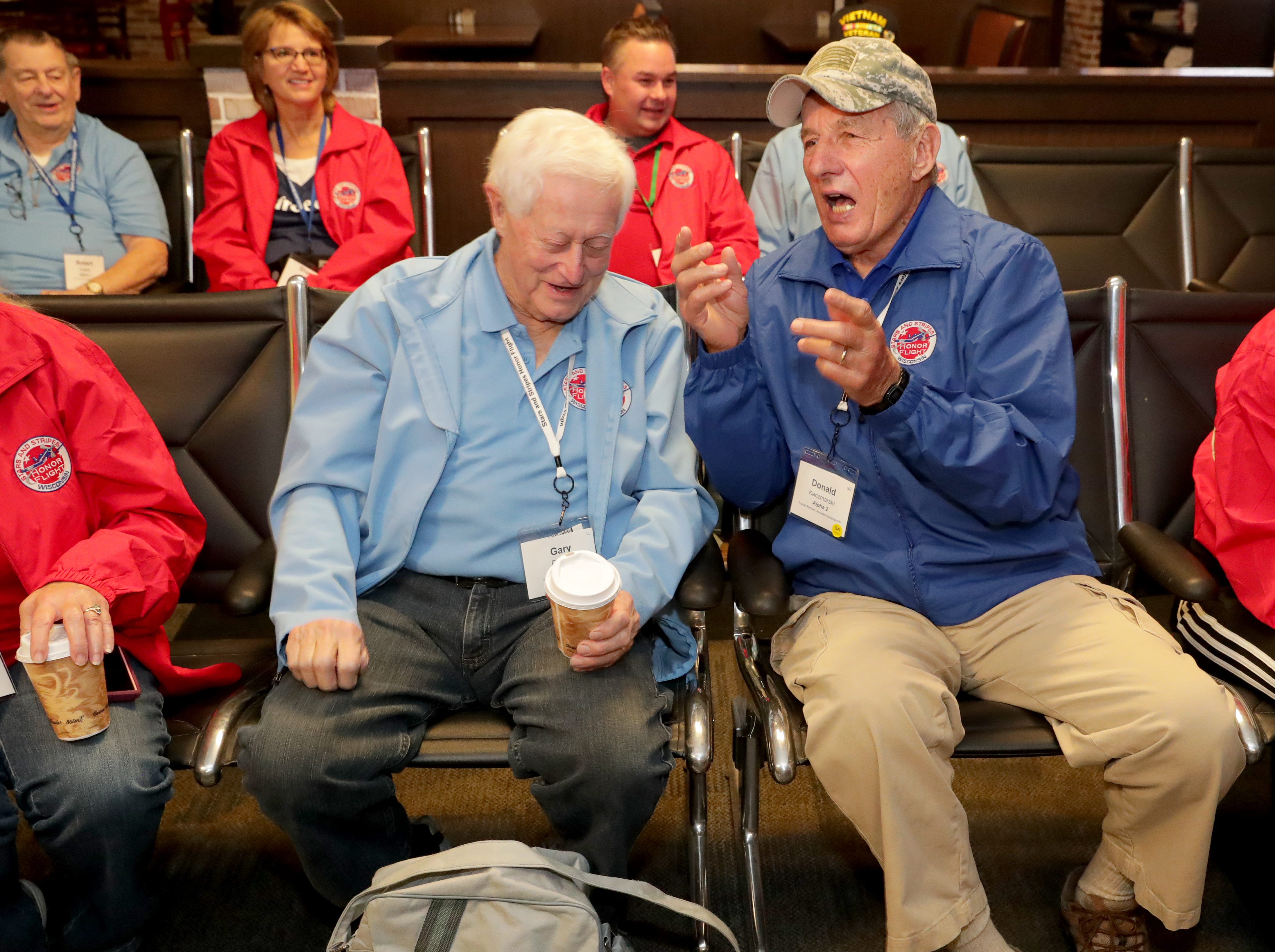 Korean War veterans Gary Grunau (left) and Donald Kaczmarski, both of the Town of Brookfield, exchange war stories while waiting for the flight to depart in Milwaukee.