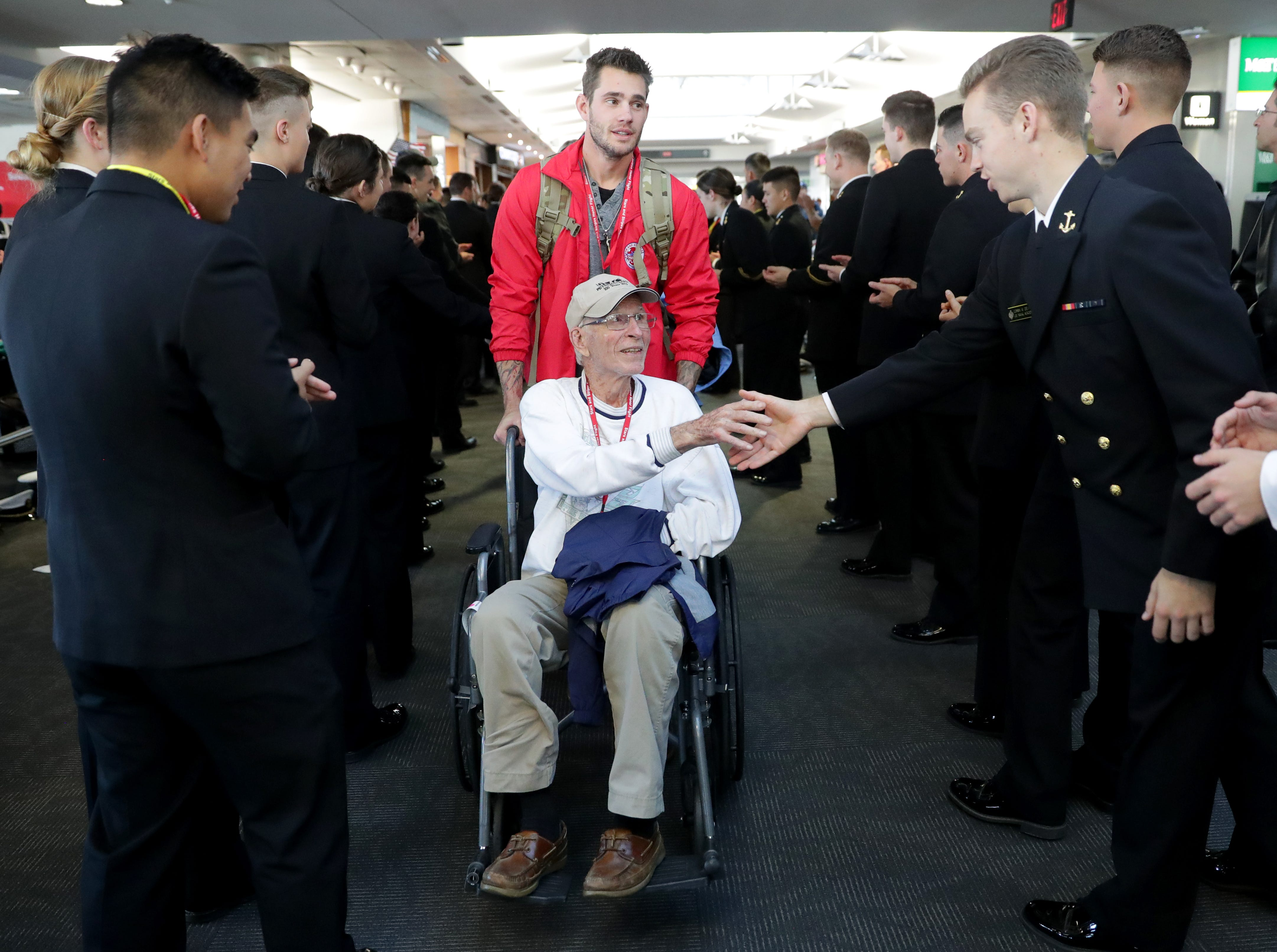 World War II Army veteran Ray Emery, 96, is greeted by midshipmen. Emery is with his grandson, Andrew Rehberg, who served two deployments in Afghanistan, 2010-'11 and 2012-'13, and in Kuwait, 2016-'17.