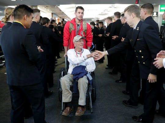 World War II Army veteran Ray Emery, 96, is greeted by midshipmen from the U.S. Naval Academy Saturday after his Honor Flight landed in Baltimore. Emery is with his grandson, Andrew Rehberg, who served two deployments in Afghanistan and one in Kuwait.