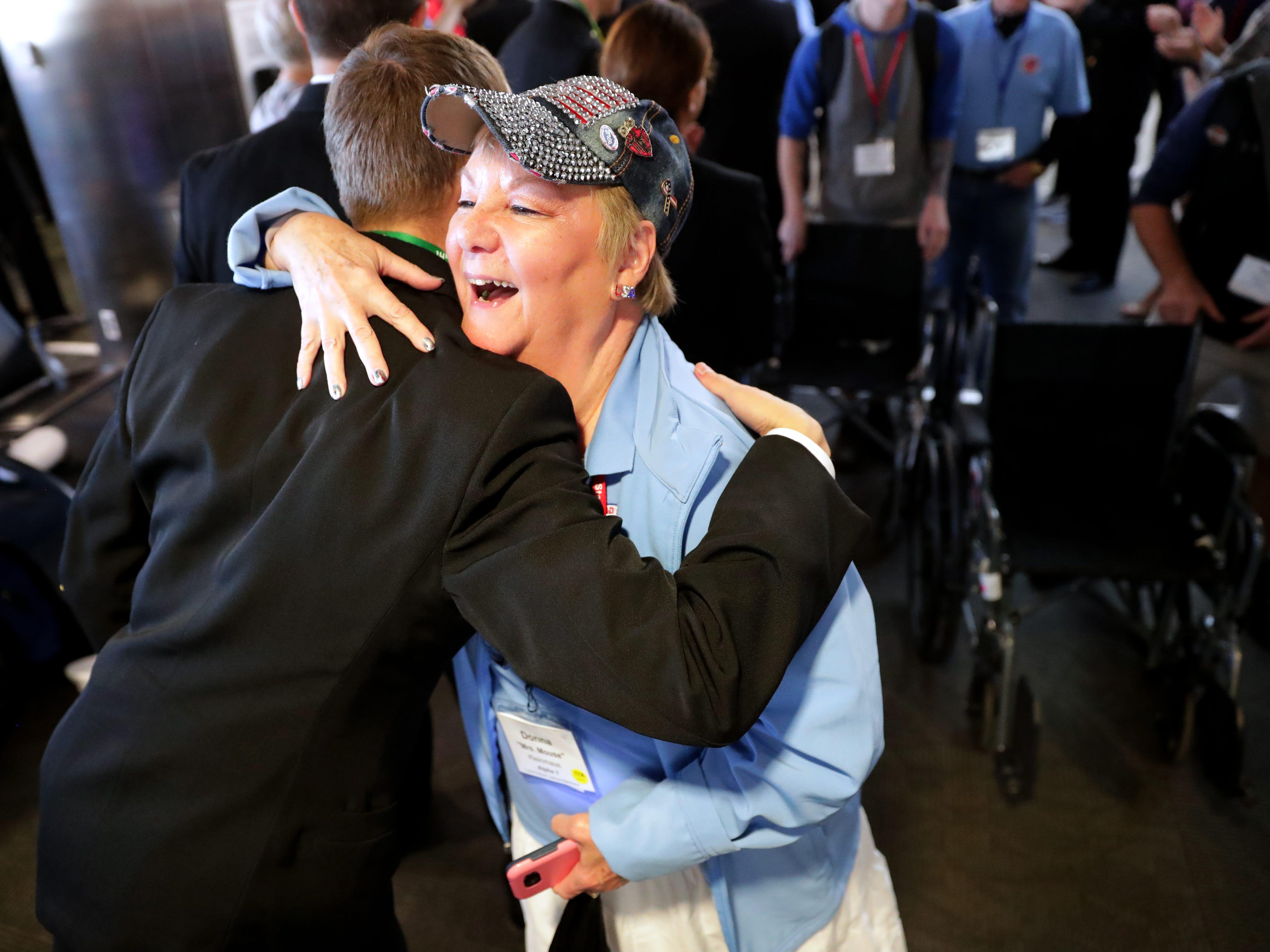 Vietnam veteran Donna Kleinmaus of West Bend hugs a midshipman after getting off the plane in Baltimore.  She flew with her husband, John Kleinmaus, also a Vietnam veteran.
