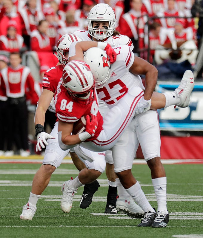 Badgers tight end Jake Ferguson is taken to the turf by Rutgers defensive back Kiy Hester but not until he picked up a first down during the first half Sartuday.