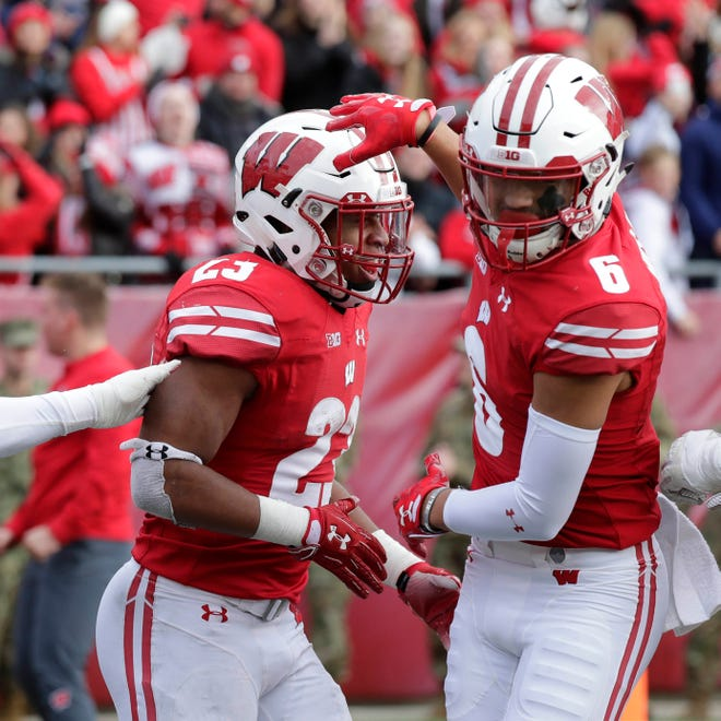 Badgers running back Jonathan Taylor (left) celebrates his second half touchdown with wide receiver Danny Davis III during Wisconsin's 31-17 win over Rutgers on Saturday at Camp Randall .
