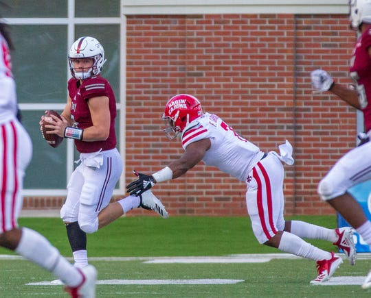 Troy's Sawyer Smith looks down the field for a receiver during the second quarter against the Ragin' Cajuns.  Ferrod Gardner chases for UL.