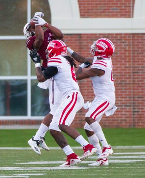 Troy's Damion Willis made this catch, one of his 10 on Saturday, over Corey Turner (left) and Michael Jacquet in a 26-16 UL loss to the Trojans that the Ragin' Cajuns would like to forget.