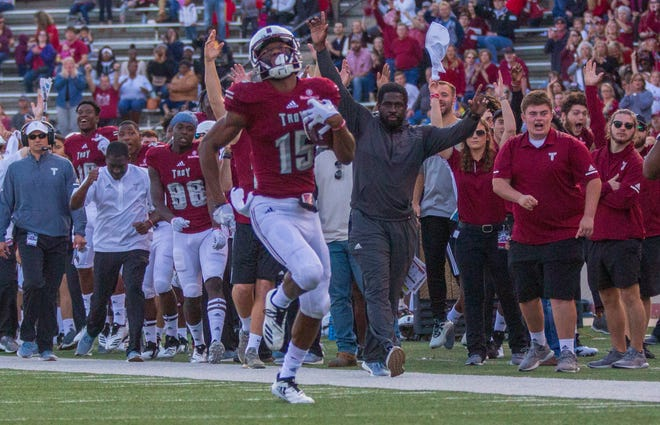 Troy's Damion Willis runs the ball in for the team's first touchdown of the game as the crowd behind him goes crazy.