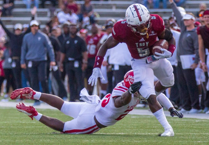 Troy's Jabir Daughtry-Frye runs the ball during the first quarter as the Ragin' Cajuns' Deuce Wallace tried for a tackle.