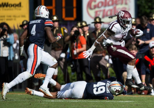 Texas A&M running back Trayveon Williams (5) hurdles Auburn linebacker Darrell Williams (49) at Jordan-Hare Stadium on Saturday, Nov. 3, 2018. Auburn defeated Texas A&M 28-24.
