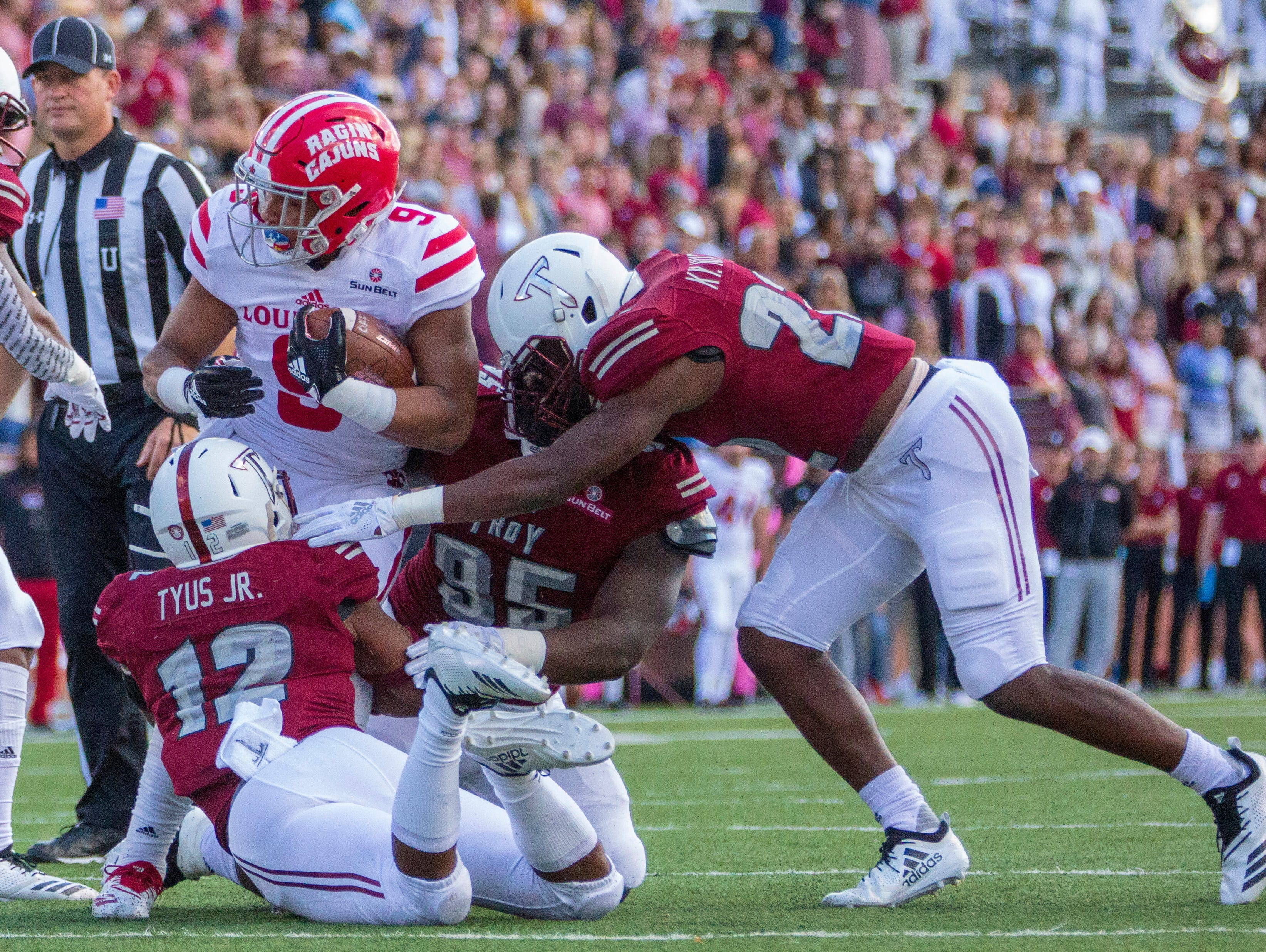 The Ragin' Cajuns' Trey Ragas runs into Troy's Melvin Tyus and Will Choloh, Jr. during the first half.