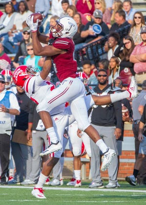 Troy's Damion Willis catches a high pass as the Ragin' Cajuns' Daijuane Dorsey tries to block him from it.