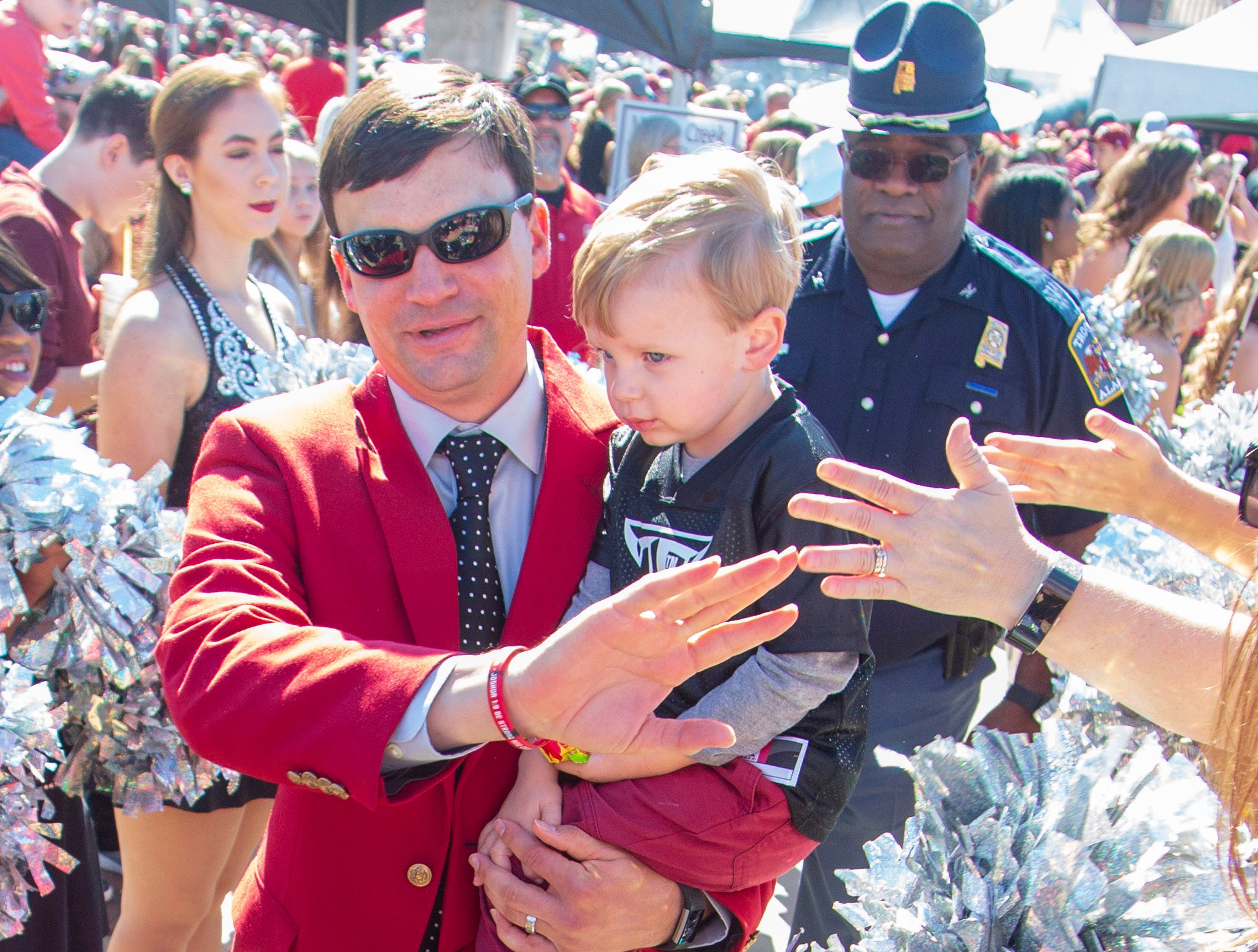 Troy's head coach Neal Brown carries his son and hands out high-fives during Trojan Walk.