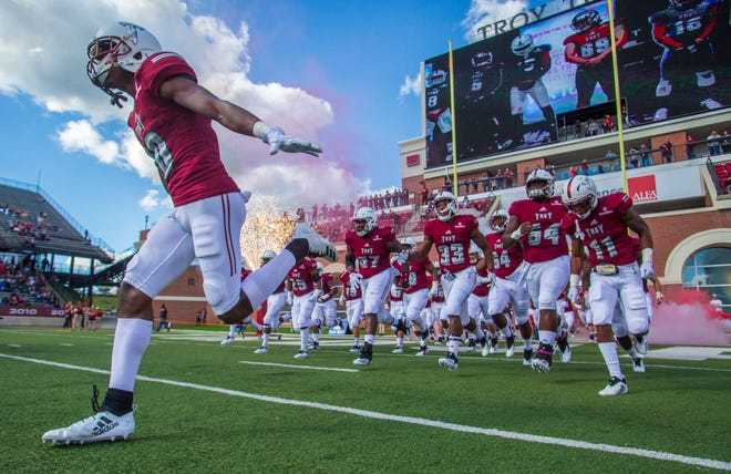 The Troy football team takes the field before kickoff against the Ragin' Cajuns.