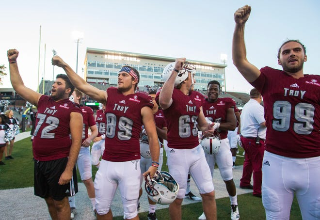 Troy's Kade McLaney, Trey Coryell and Evan Legassey celebrate their 26-16 win over the Ragin' Cajuns.