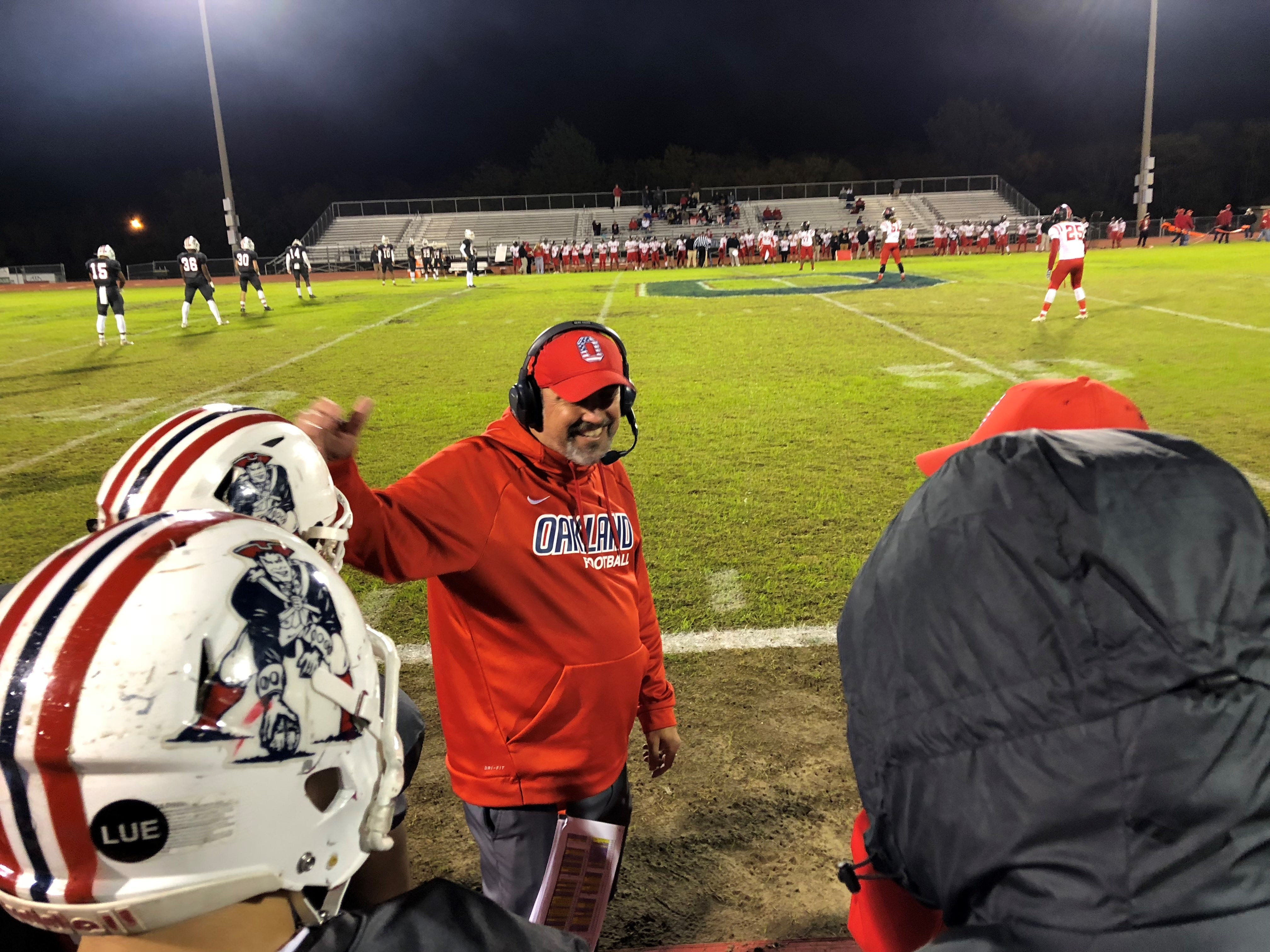 Oakland coach Kevin Creasy talks to players at the beginning of Friday's 6A playoff matchup against Rossview. The Patriots won 49-10.