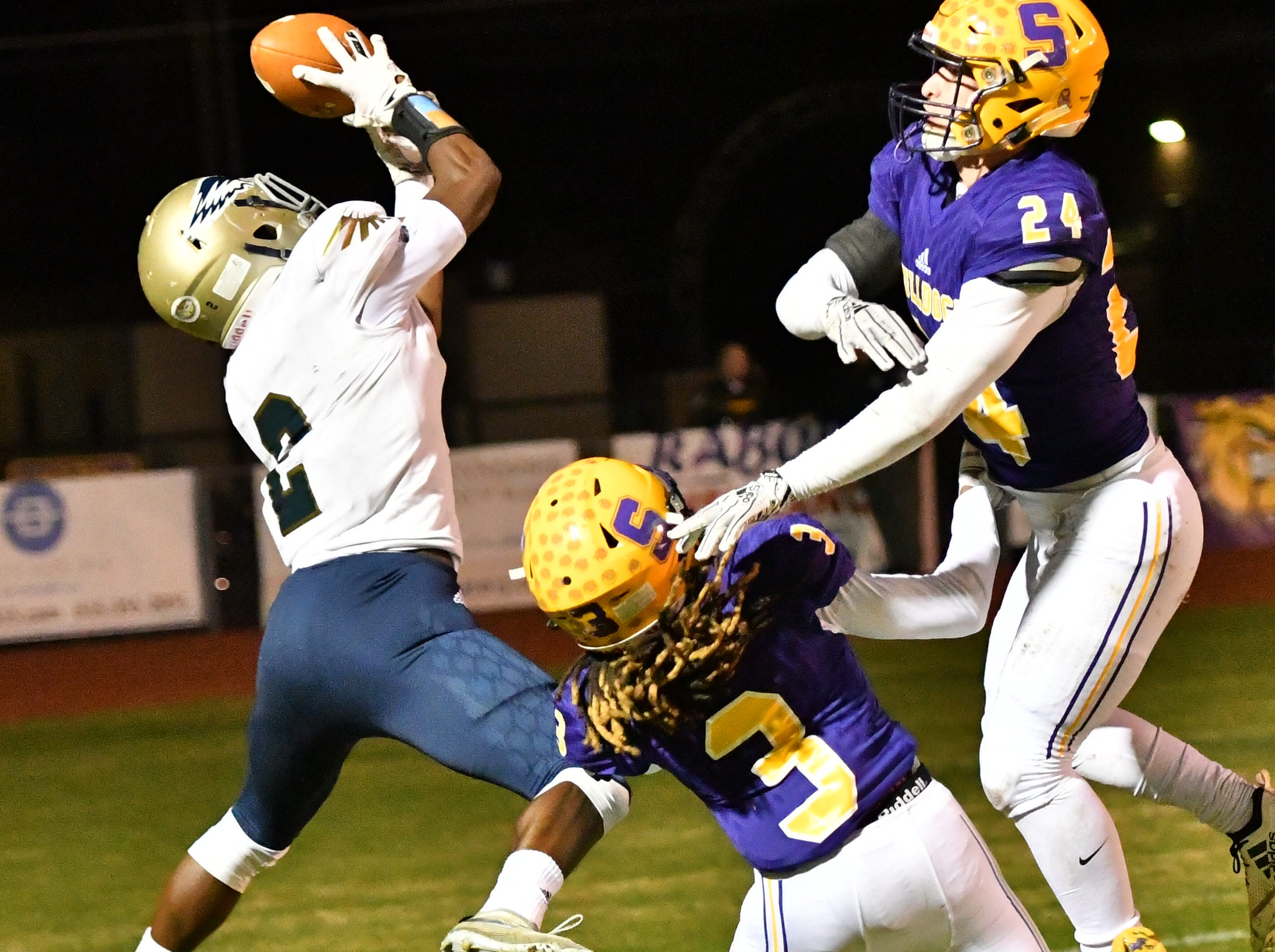 Independence wide receiver T.J. Sheffield hauls in a catch as Smyrna's Austin Guidry and Da'shawn Moore (3) defend.