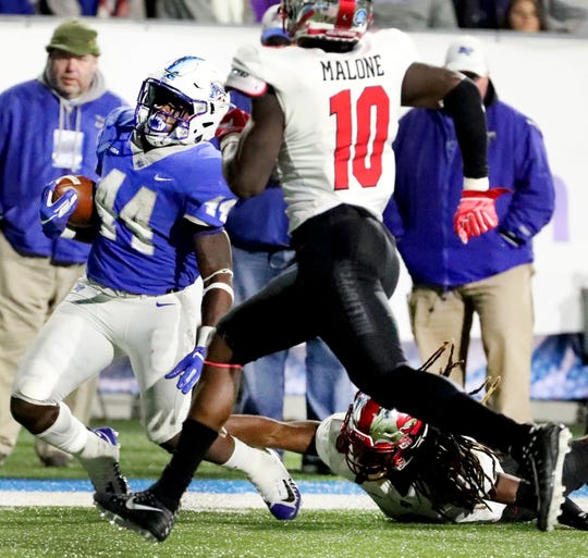 MTSU's Chaton Mobley (44) runs the ball as Western Kentucky's Drell Greene (9) and Deangelo Malone (10) try to stop him during the game at MTSU on Friday, Nov. 2, 2018.