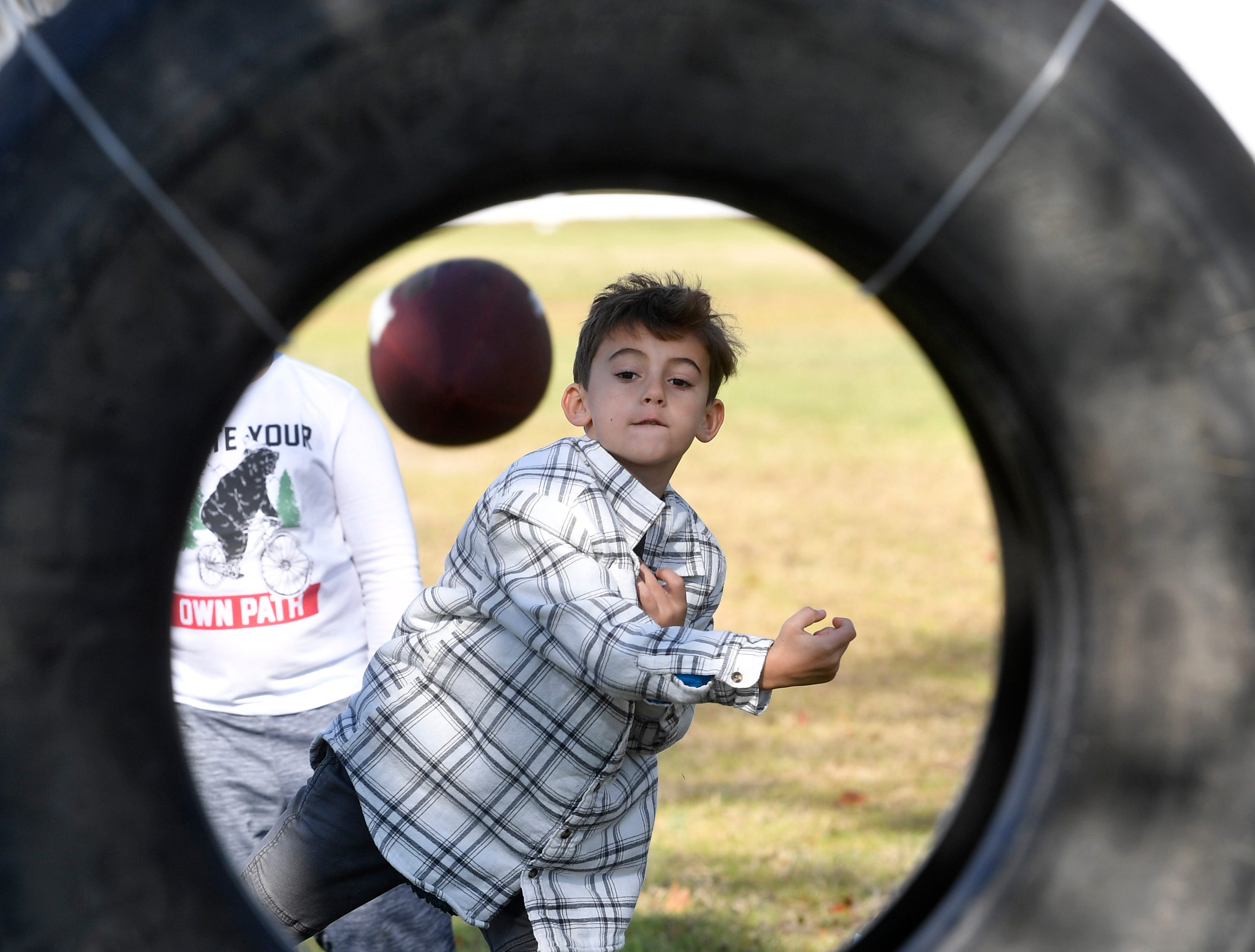 Lincoln Travis shows he know how to get the football through the tire during Family Day at the Park at Harlinsdale Farms Saturday Nov. 3, 2018, in Franklin, Tenn.