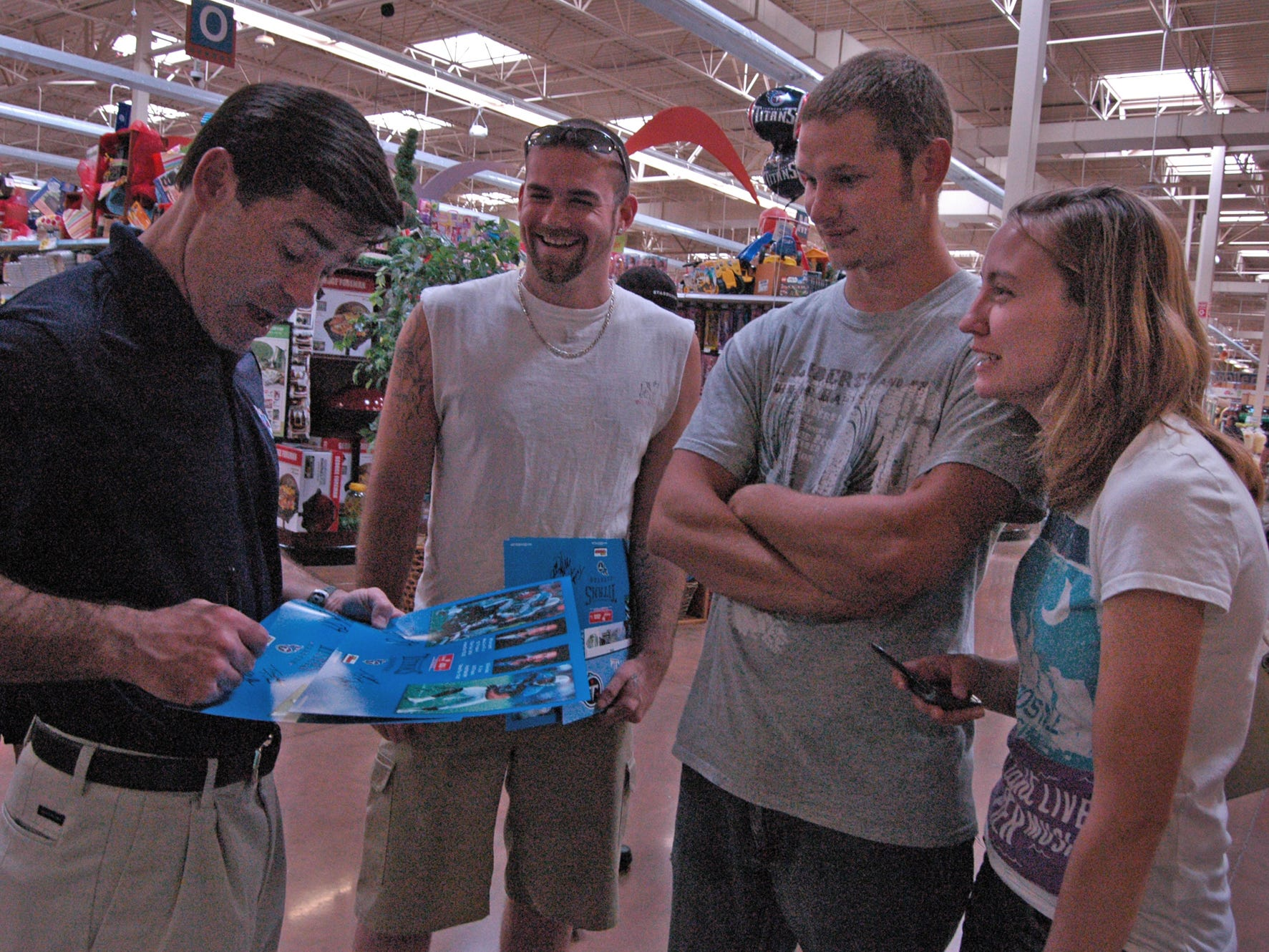 From left: Voice of the Titans Mike Keith signs autographs for Josh Allen, Jeremy Sellars and Cindy Harness, all of Gallatin, during the Caravan For Kids at the Kroger Marketplace in 2012.