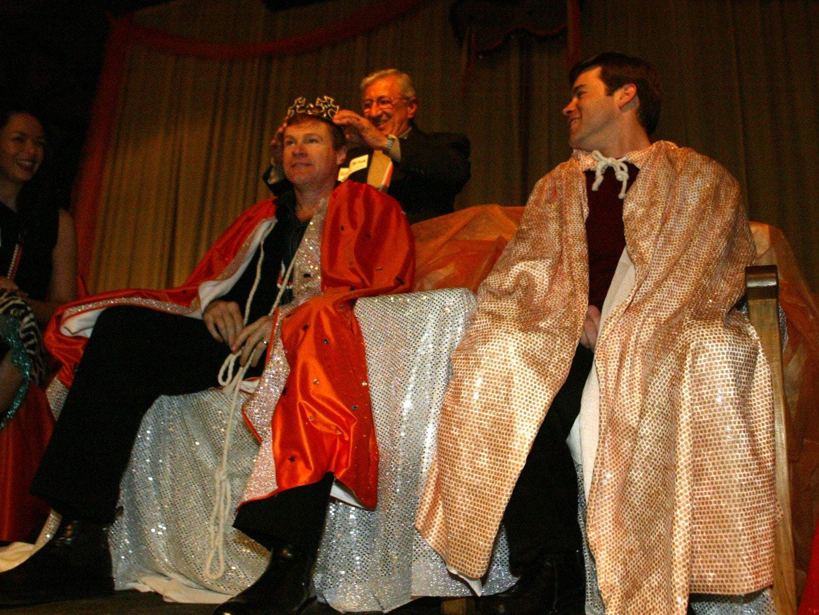 Actor David Keith, left, and his cousin Mike Keith (the voice of the Titans) are crowned grand marshals by University of Tennessee music professor George Blitzas during the Fat Orange Tuesday celebration at the Factory in Franklin in 2003.