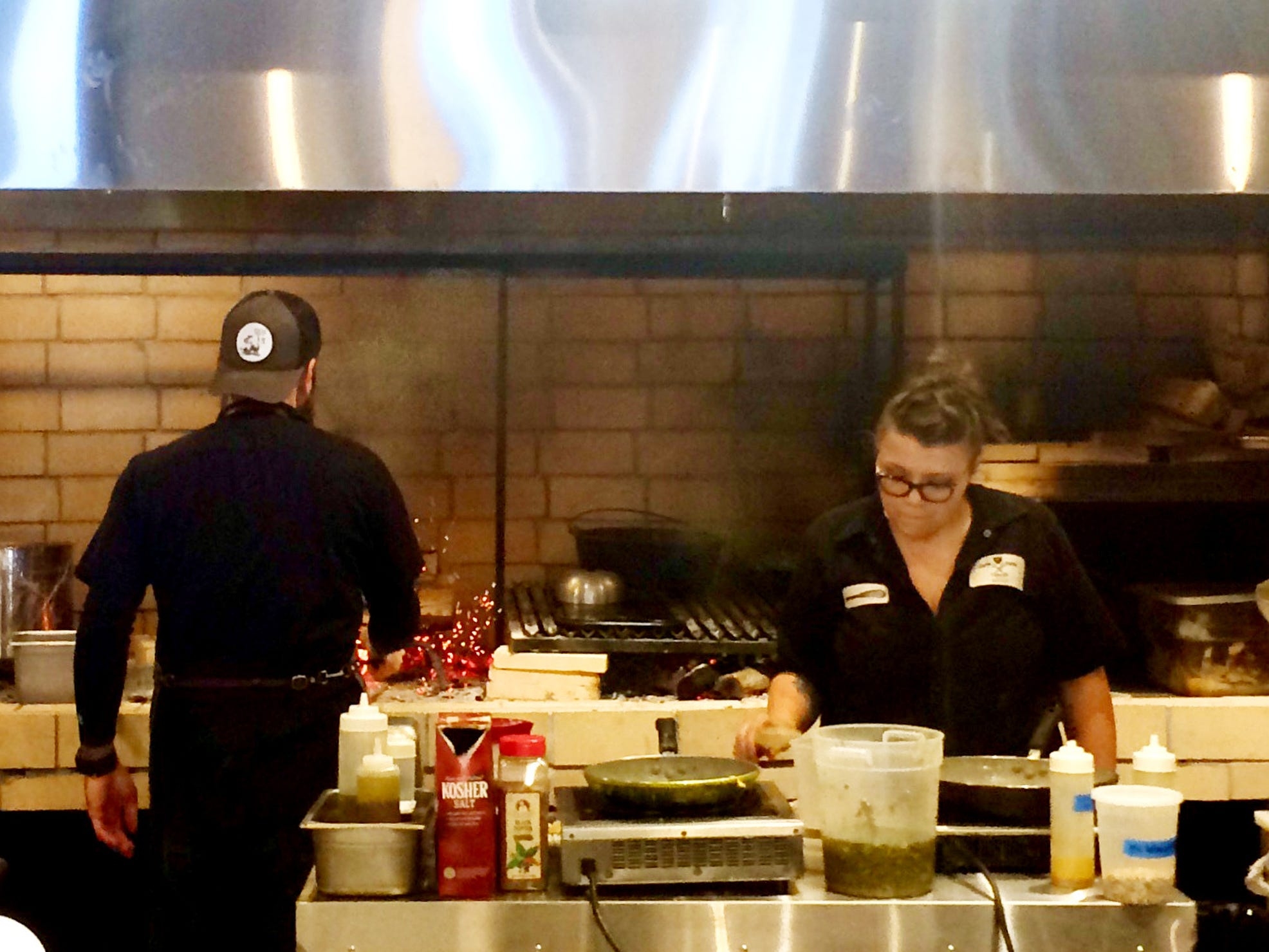 Chefs Nick and Audra Guidry, cooking in the open kitchen of Pelican+Pig.