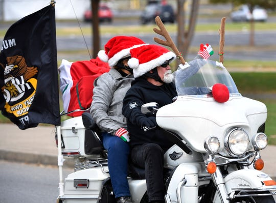 Riders wave to those on the downtown sidewalks as for the 24th year, Boswell's Harley-Davidson is partnering with the MNPD for Saturday's Annual Toy Parade, a significant fundraising event for the police department's Christmas Basket Program benefiting needy Nashville families Saturday Nov. 3, 2018, in Nashville, Tenn.
