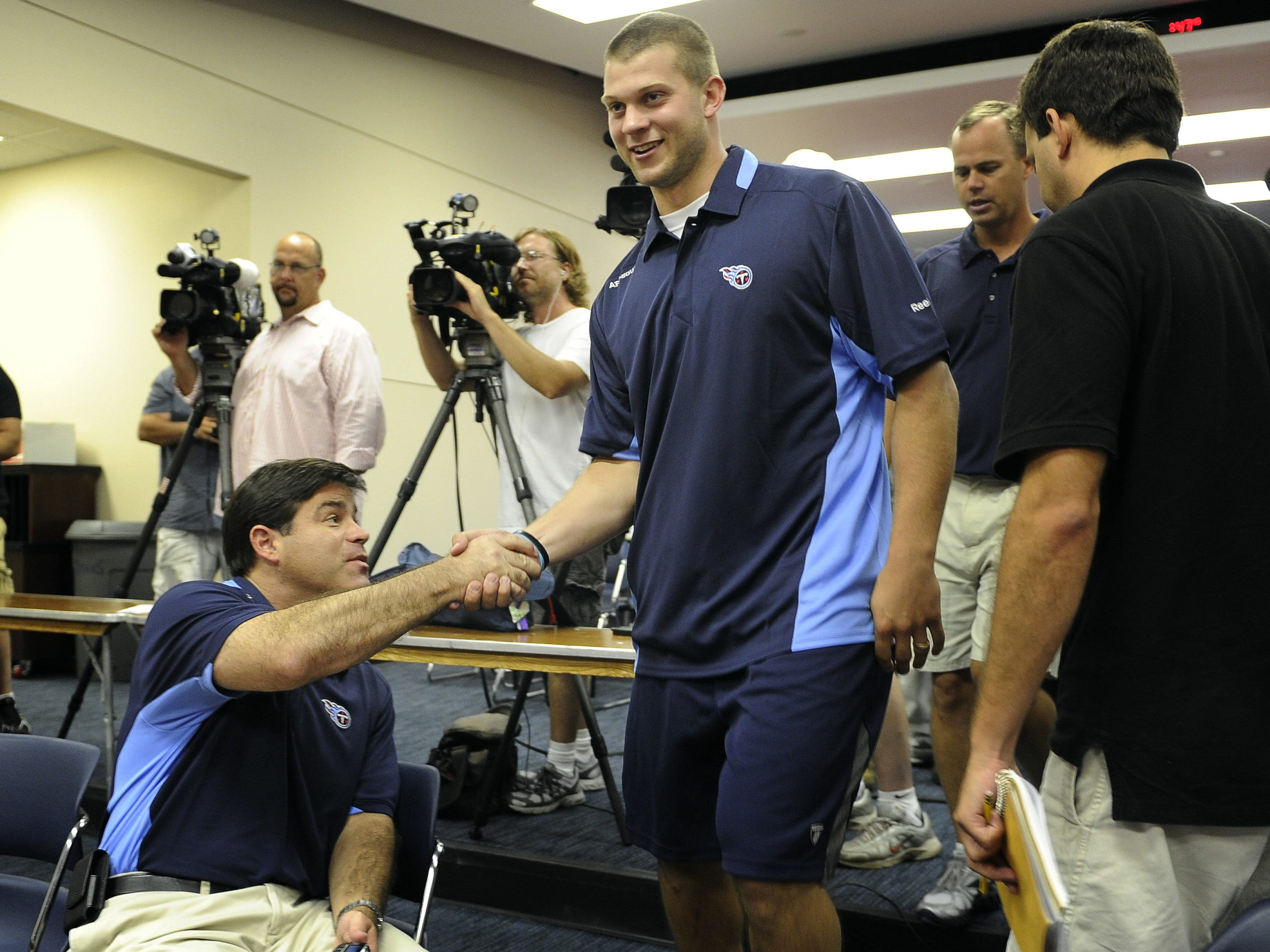 Titans radio personality Mike Keith shakes hands with Titans first-round draft pick Jake Locker as he enters a press conference at Baptist Sports Park Friday July 29, 2011.